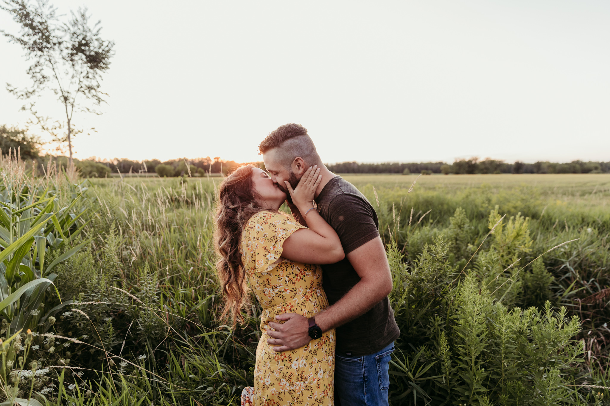 heterosexual couple kissing during sunset in a corn field