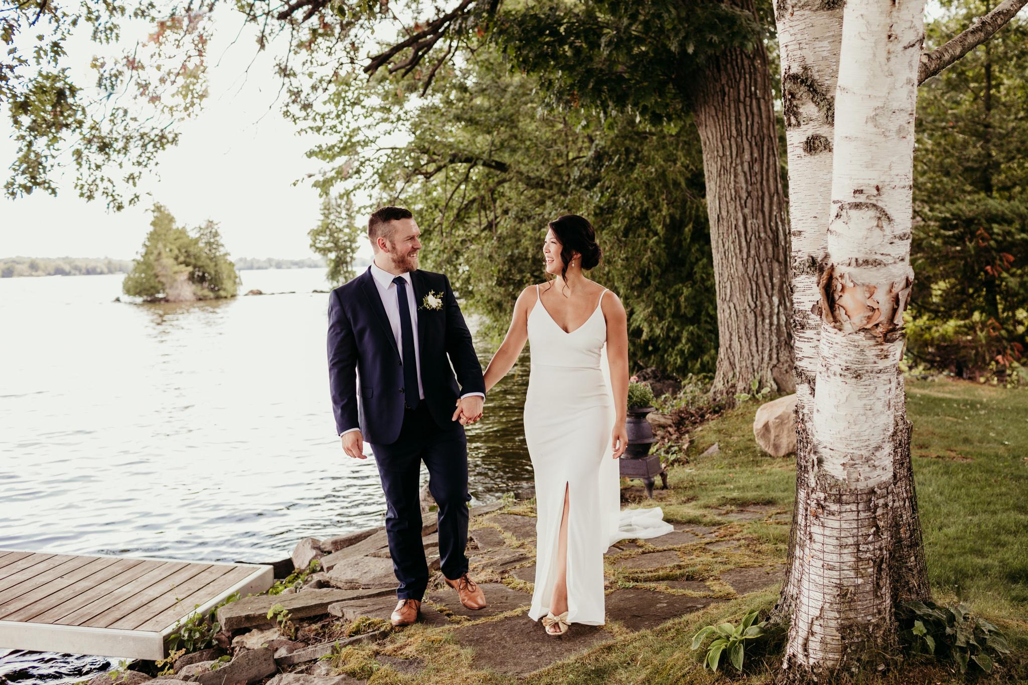 bride and groom walking lake side on Sturgeon Lake