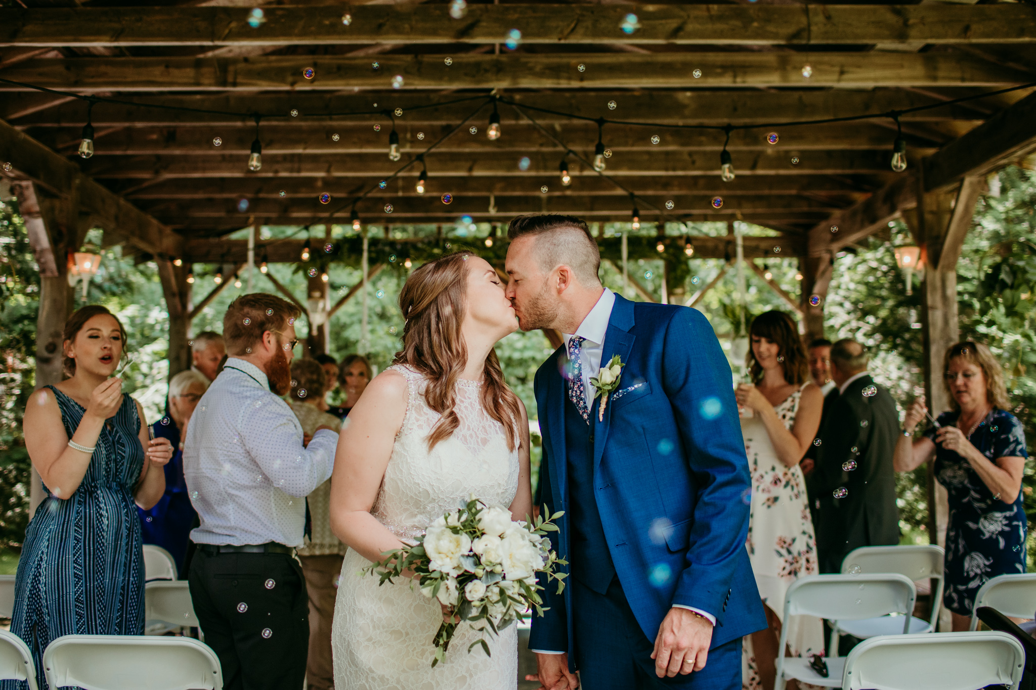 bride and groom sharing kiss after exit from reception with bubbles floating in the air
