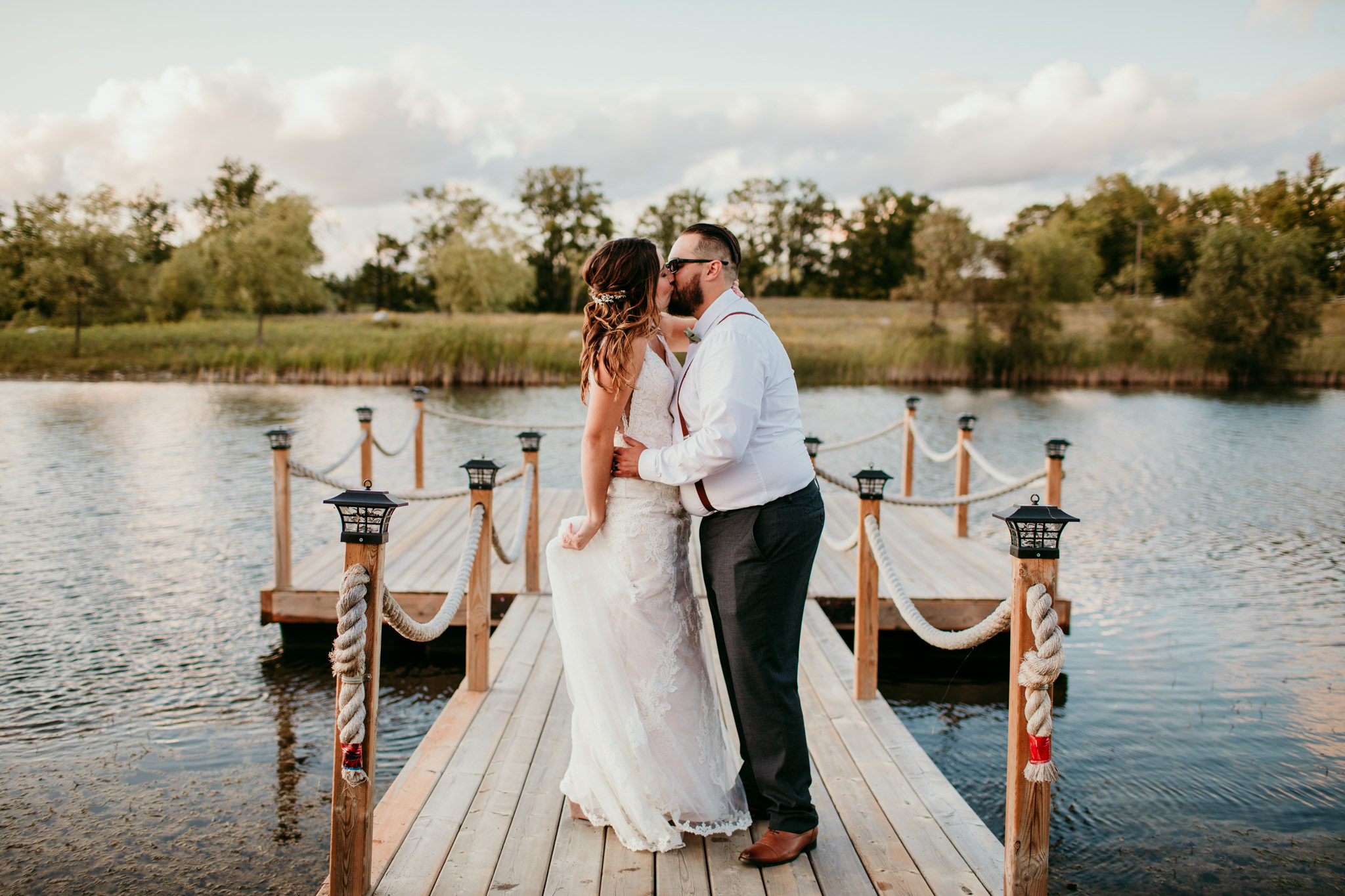 bride and groom kissing on a dock on the lake during their sunset wedding