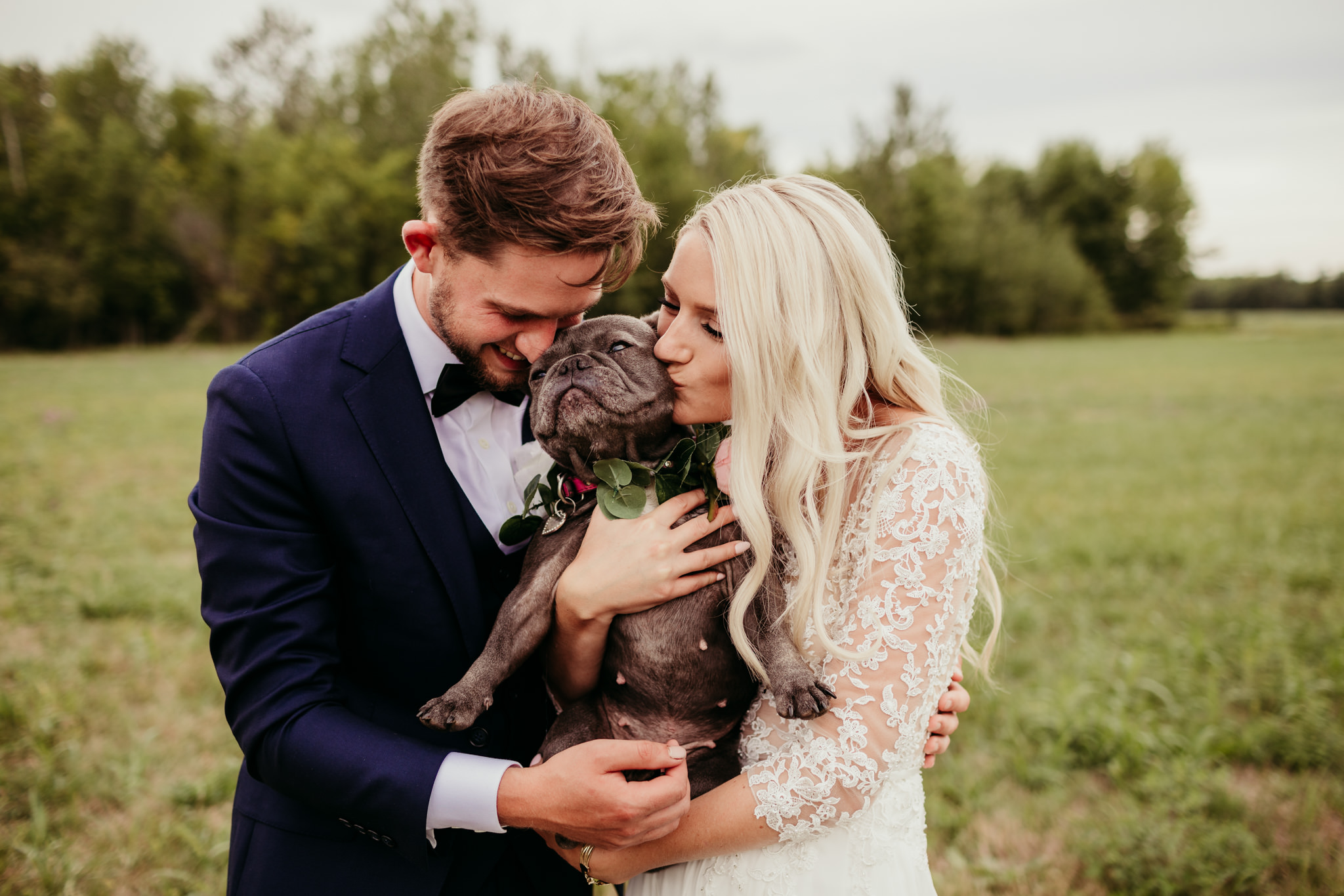 bride and groom kissing a dog they are holding while standing in a field