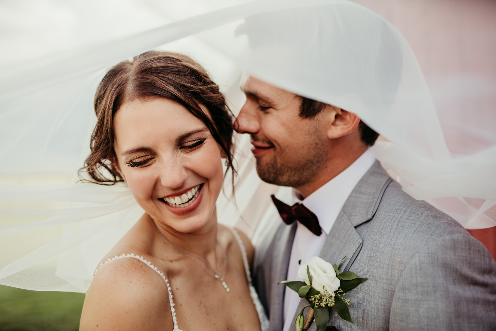 newly married girl with veil over her head laughing while husband smiling towards her ear