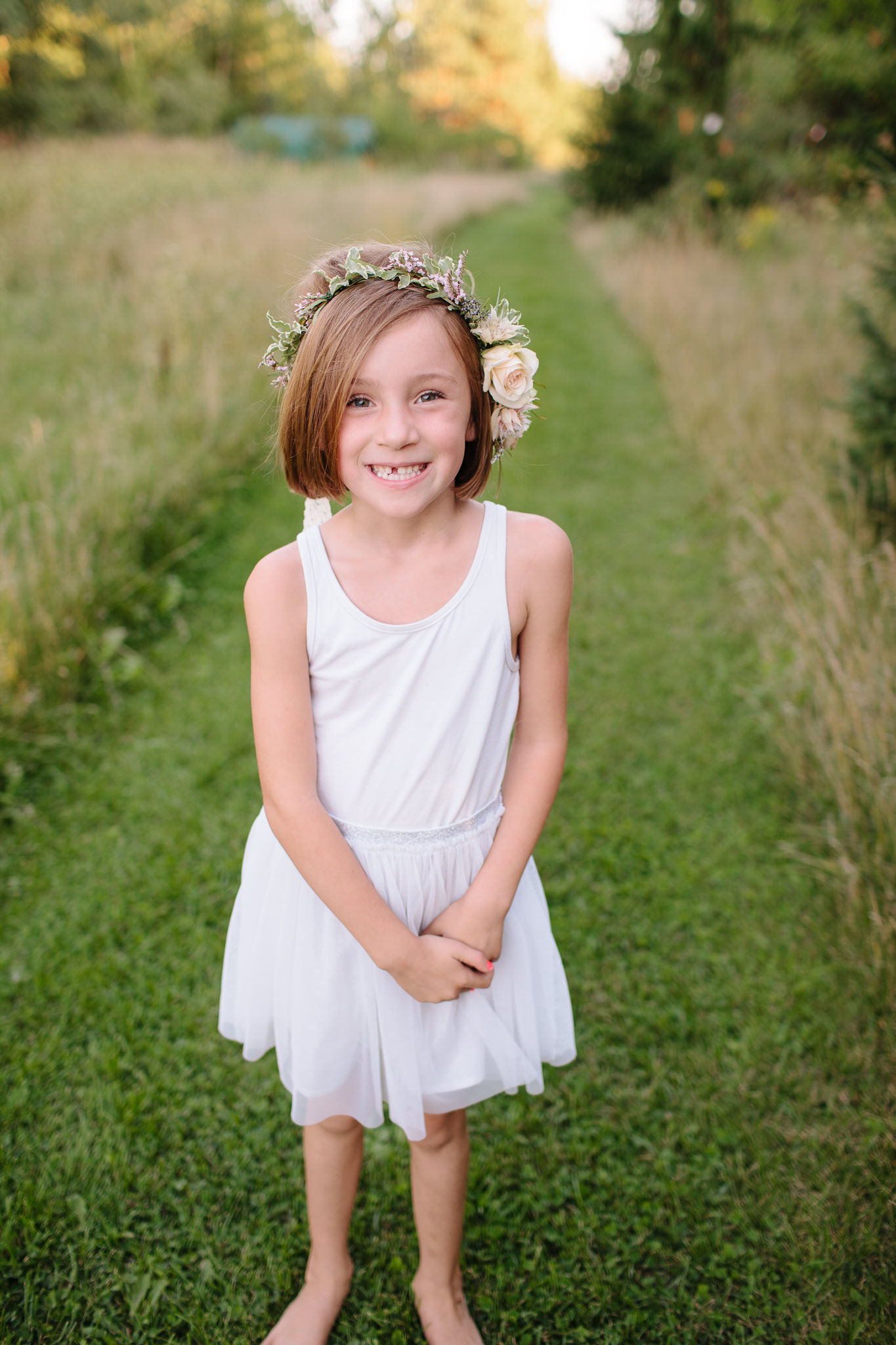girl standing in grass smiling for picture