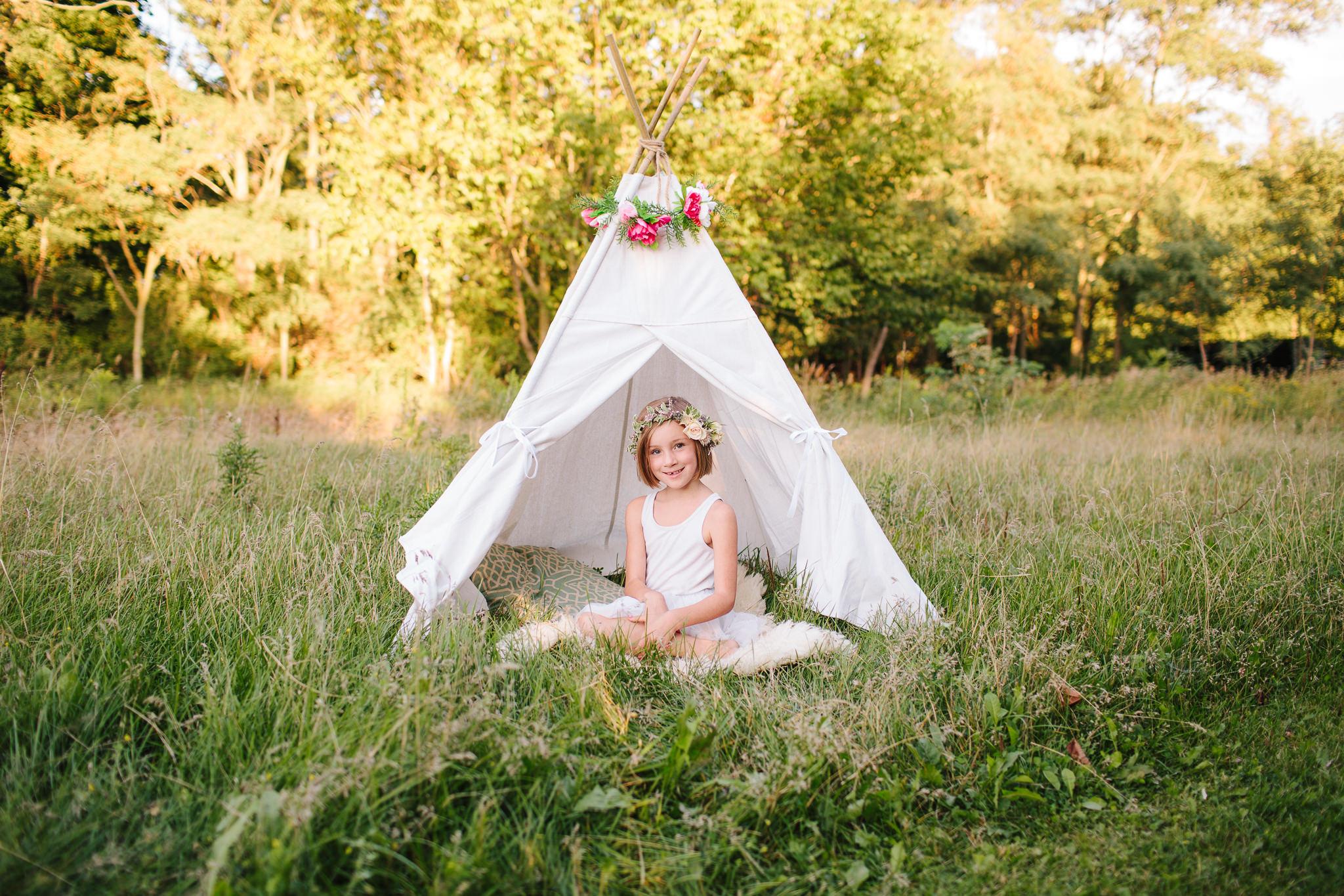 girl sitting in teepee in lindsay on field