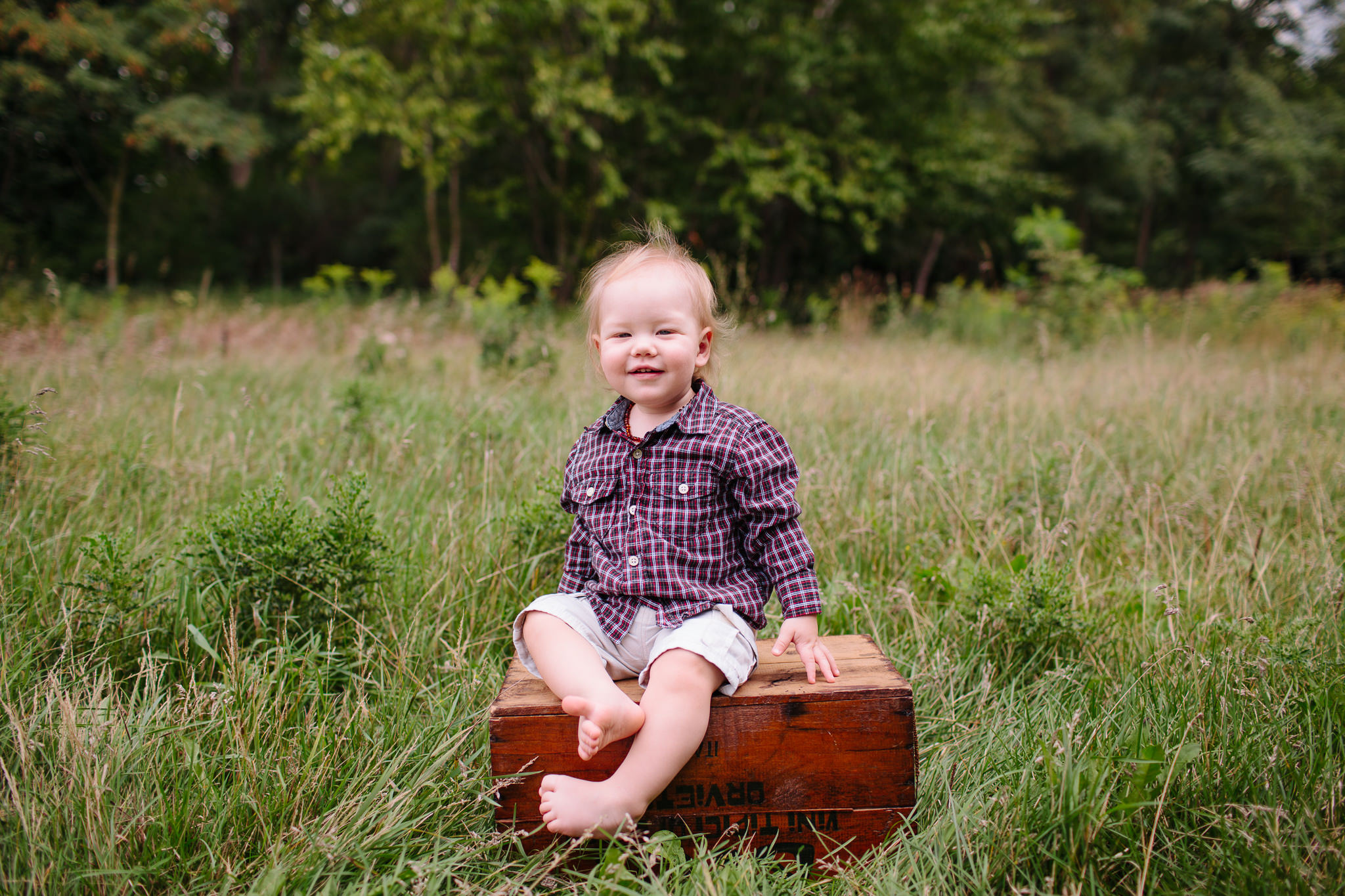 toddler sitting on box in field smiling