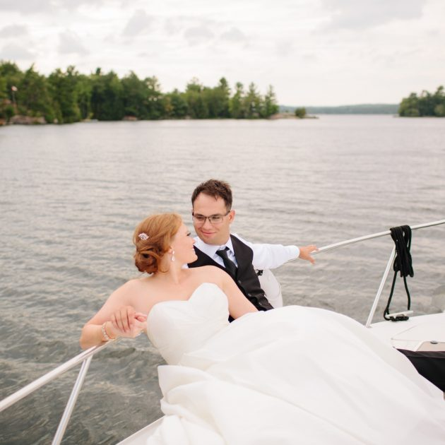 bride and groom smiling at each other on boat