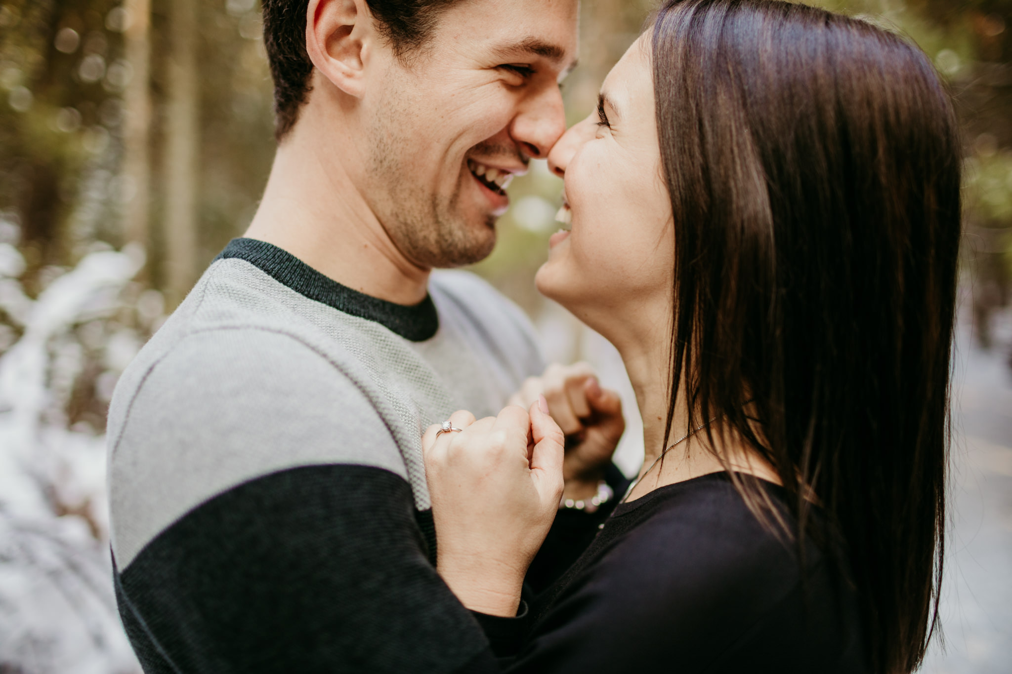 girl and boy standing nose to nose laughing while showing off her engagement ring