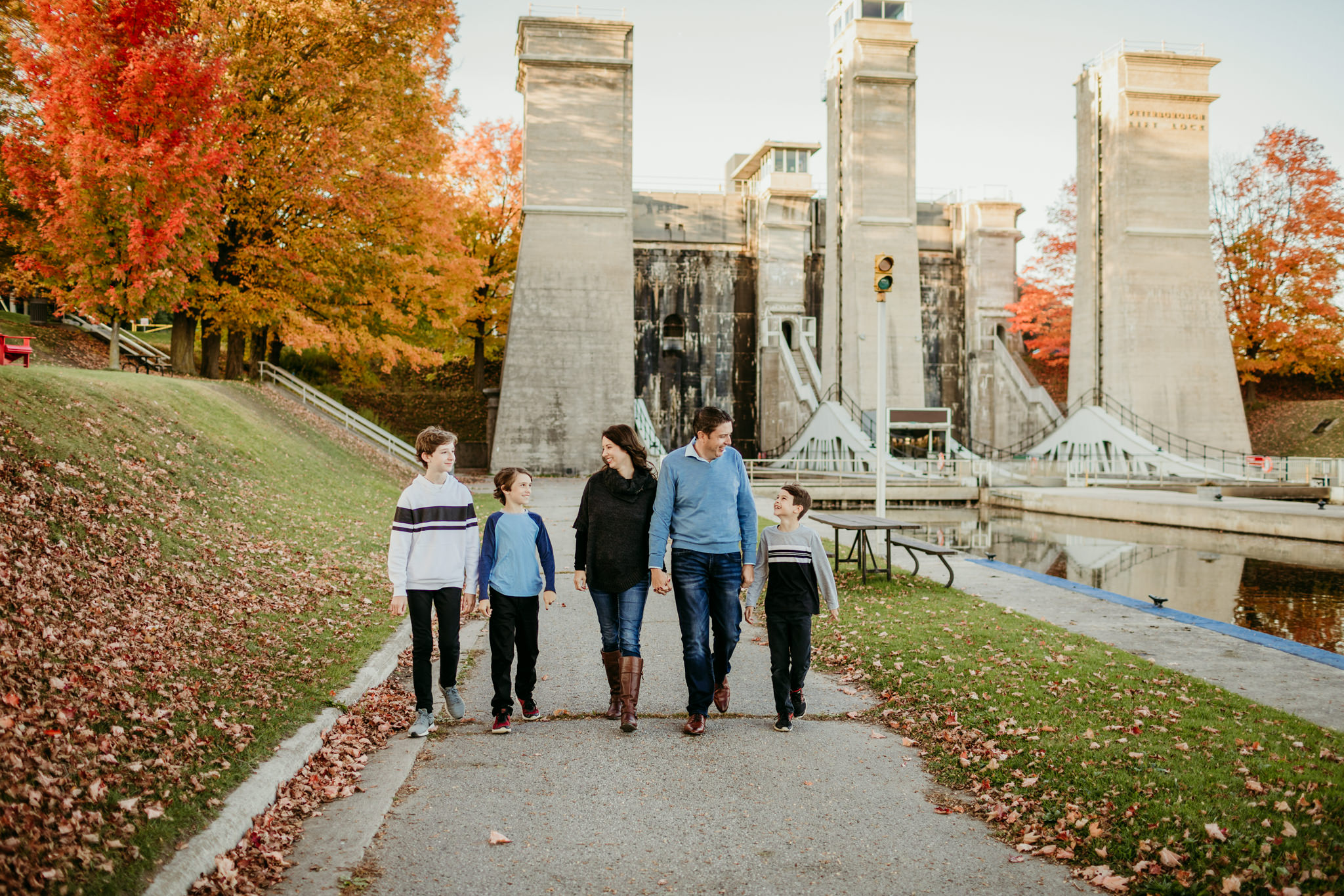 family walking hand in hand along sidewalk at lift lock in Peterborough