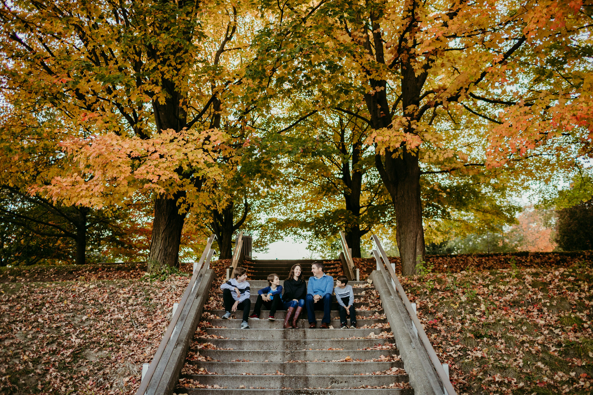 family sitting on stairs laughing together while being surrounded by fall trees at peterborough lift lock