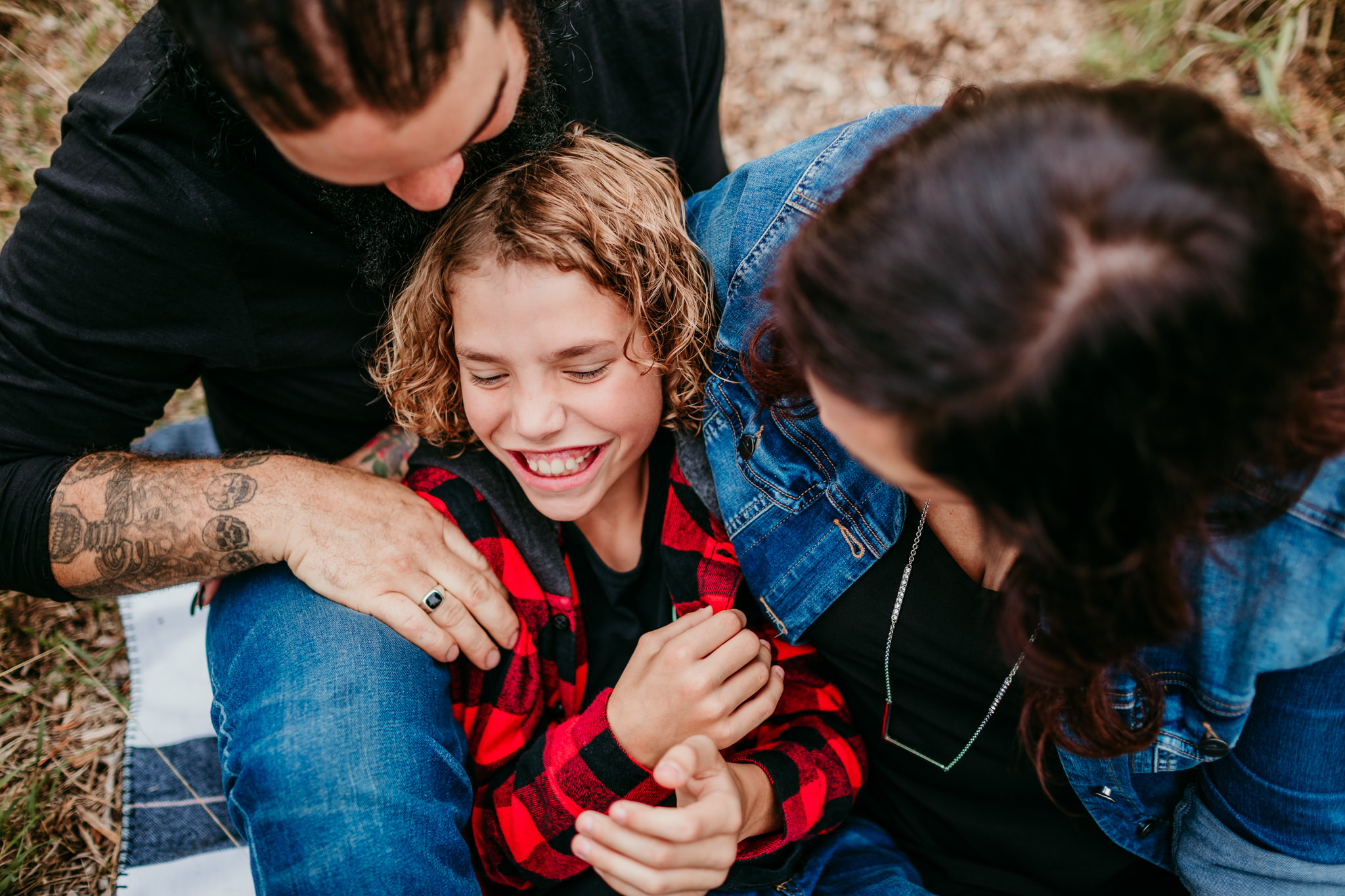 boy laughing while being tickled by his parents