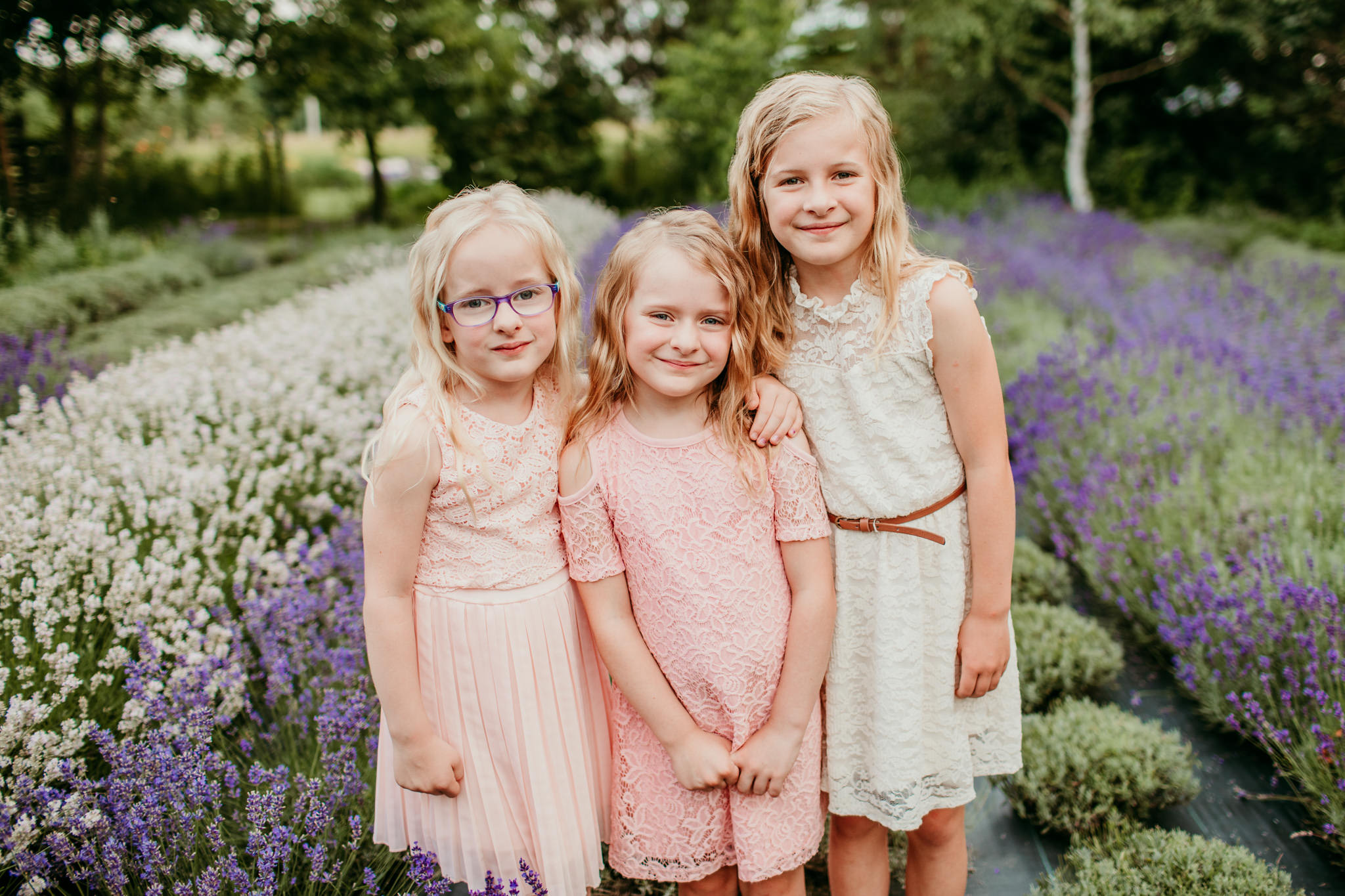 three sisters hugging together while standing in a lavender field