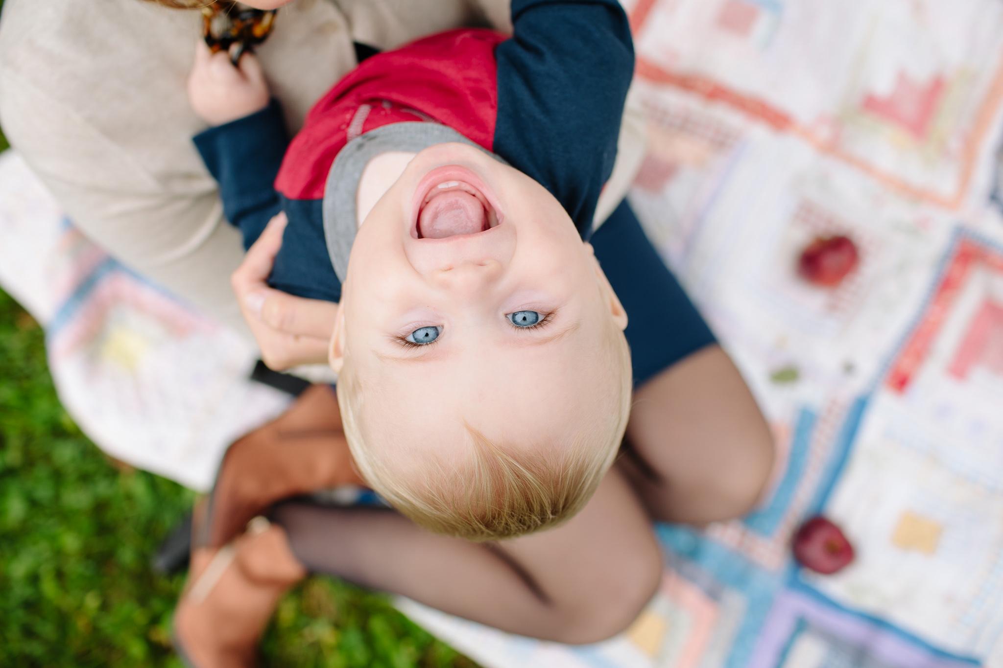 boy hanging upside down smiling