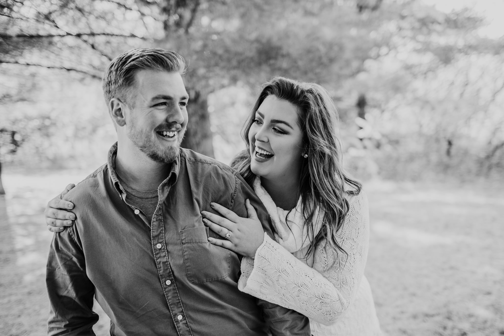 black and white image of a couple laughing together while bride looks at groom