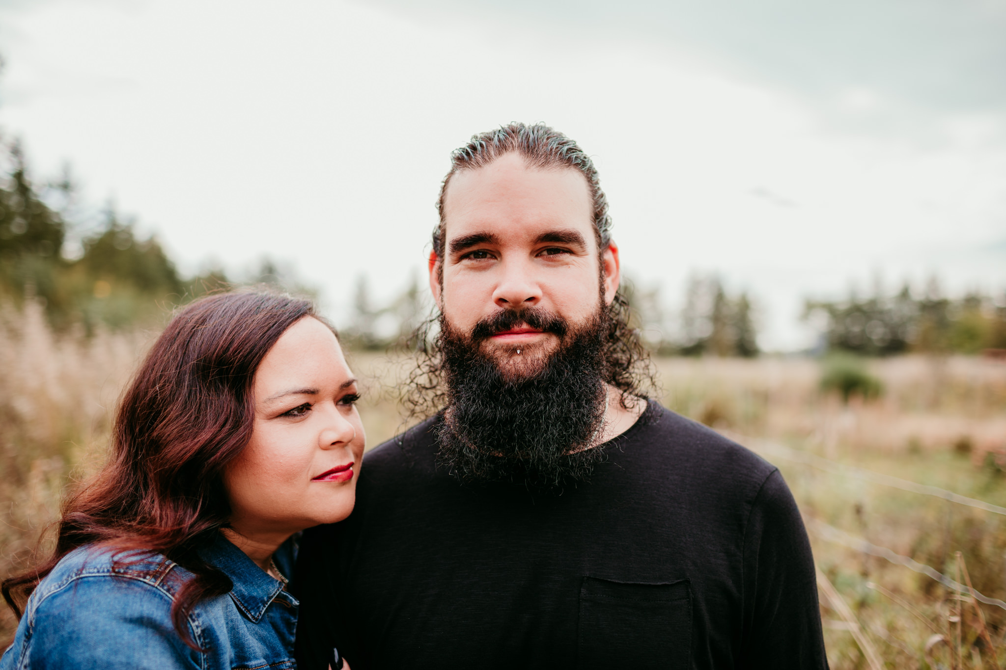 guy looking straight on at camera with beard and girl resting head on his shoulder looking into the distance