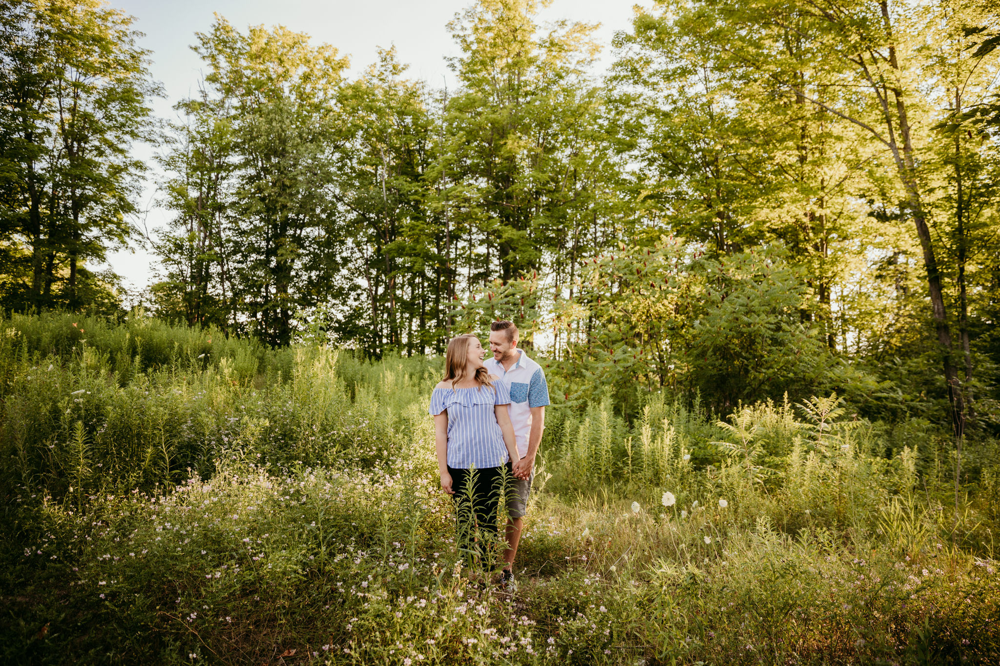 couple standing in green field with sunlight filtering in while holding hands and looking at each other