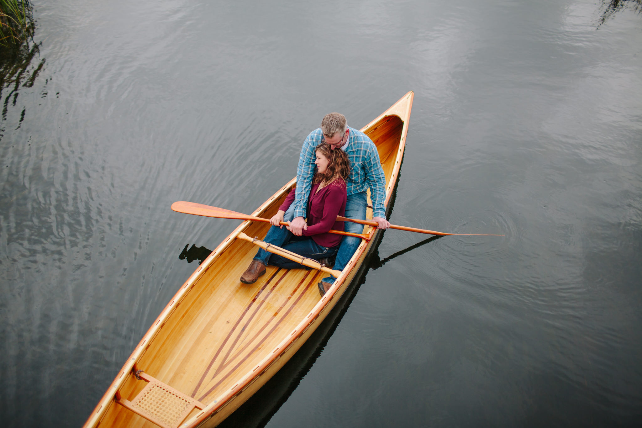 engaged couple in canoe on lake