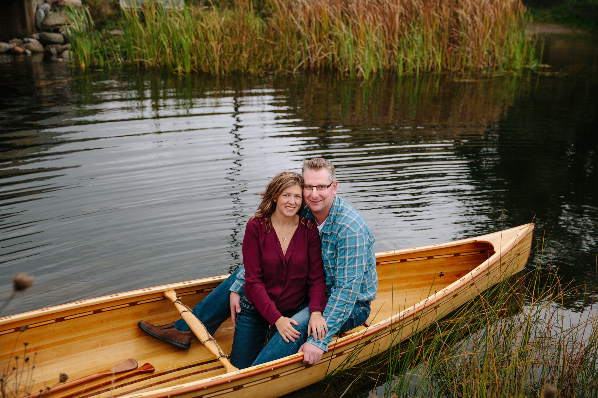 engaged couple smiling in a canoe while in the water on canoe