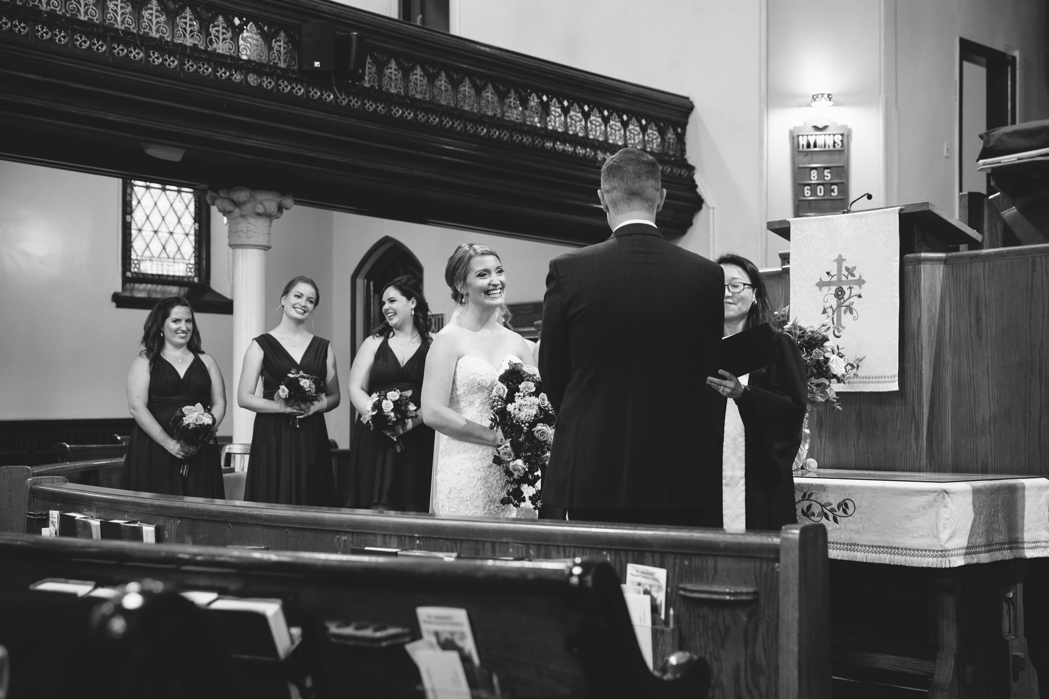 bride smiling in ceremony at groom in St. Andrews Church Lindsay, ON