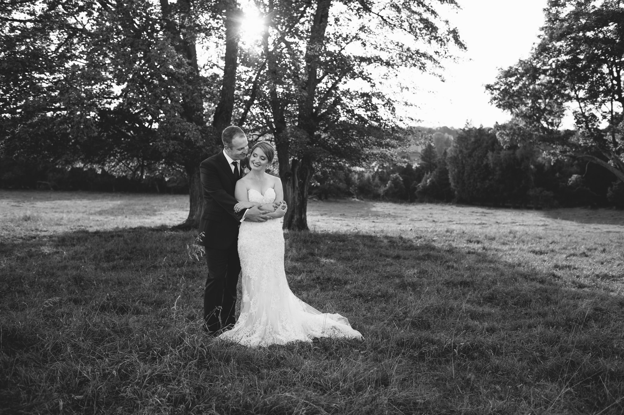 Bride and Groom Embracing each other under tree