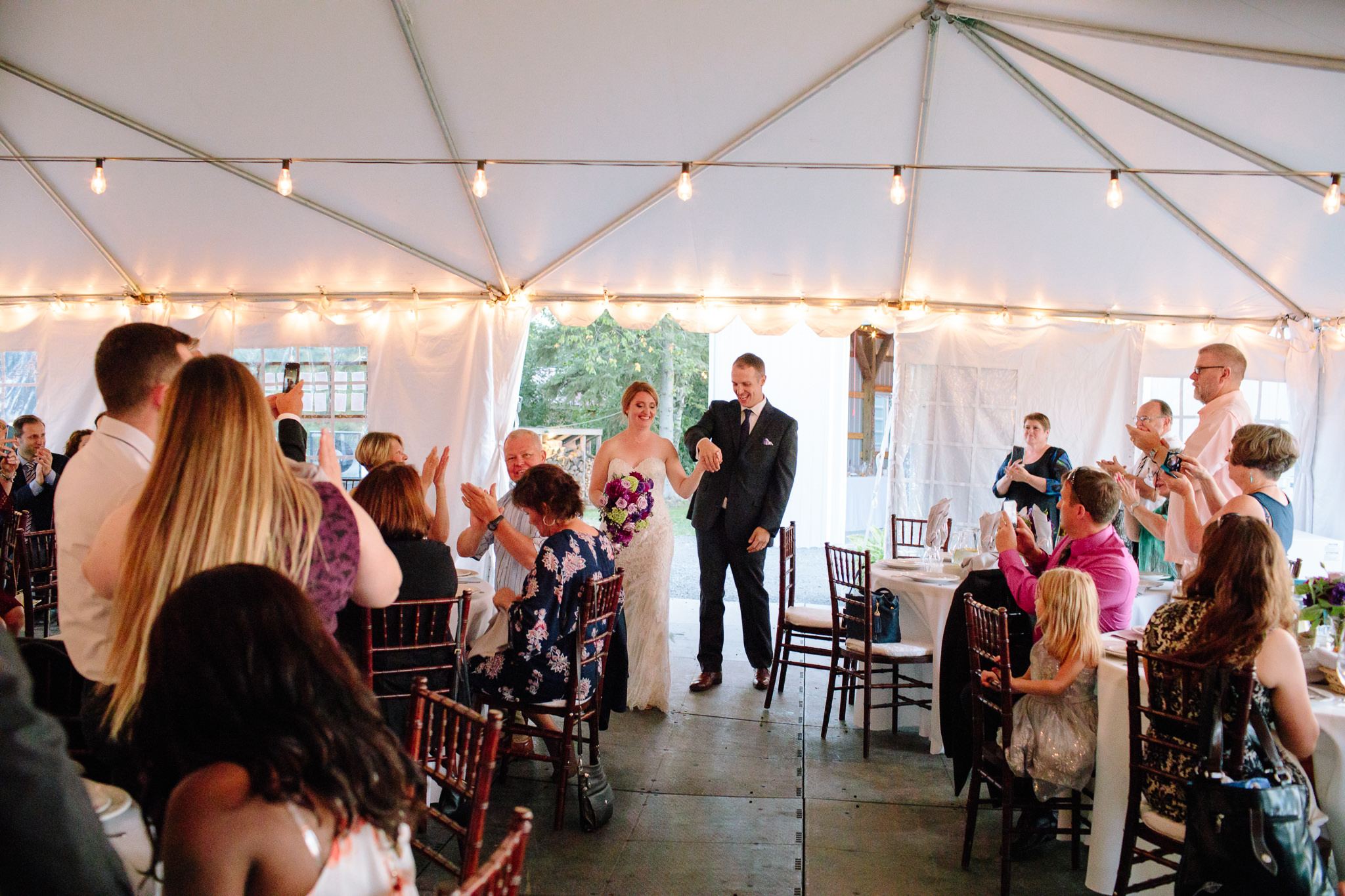 bride and groom enter tent