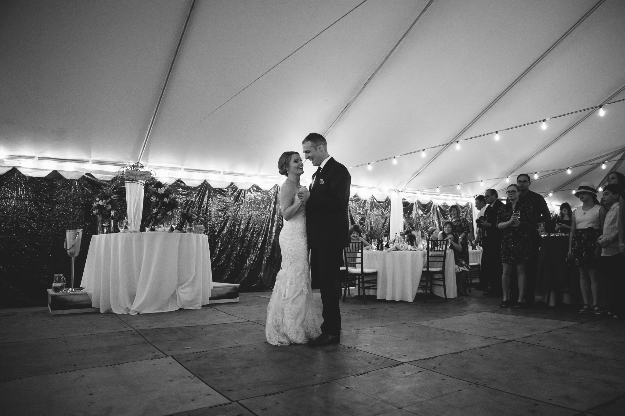 bride and groom first dance under tent in their backyard