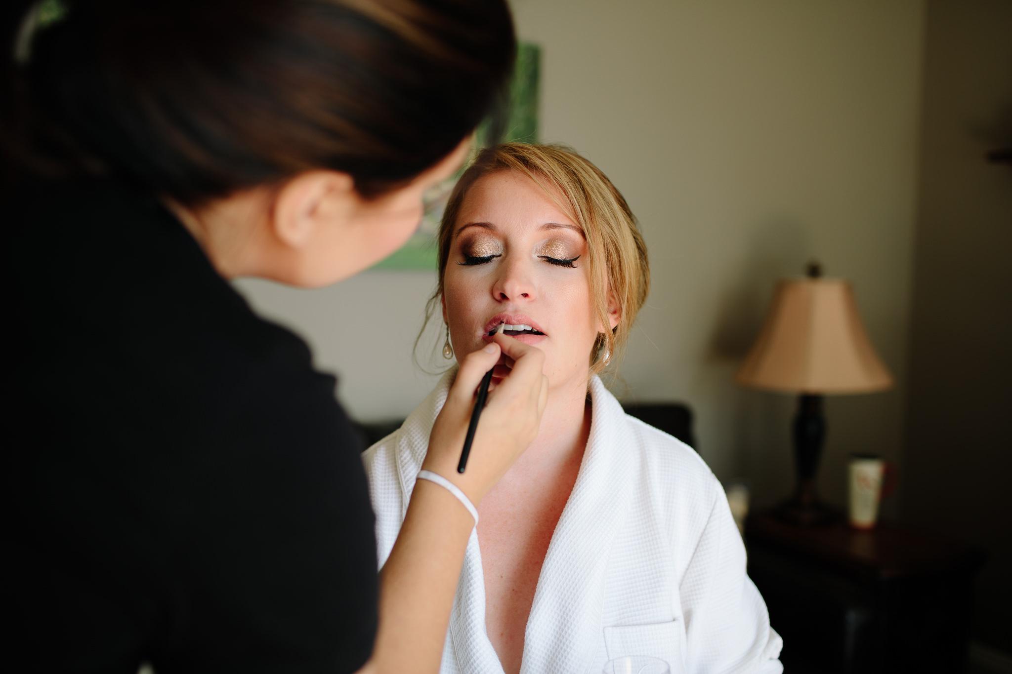 bride having makeup applied before wedding