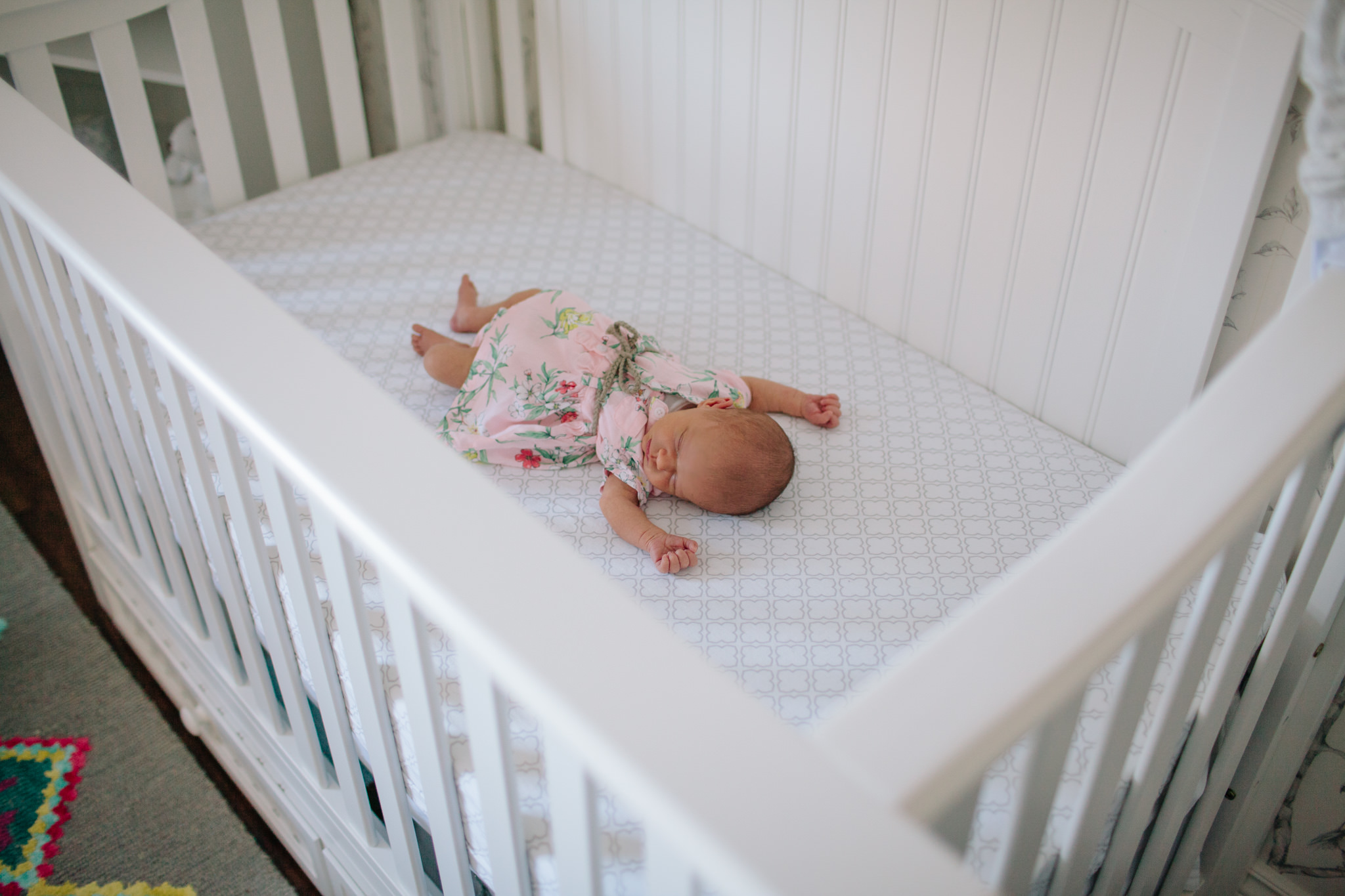 newborn girl laying in her crib