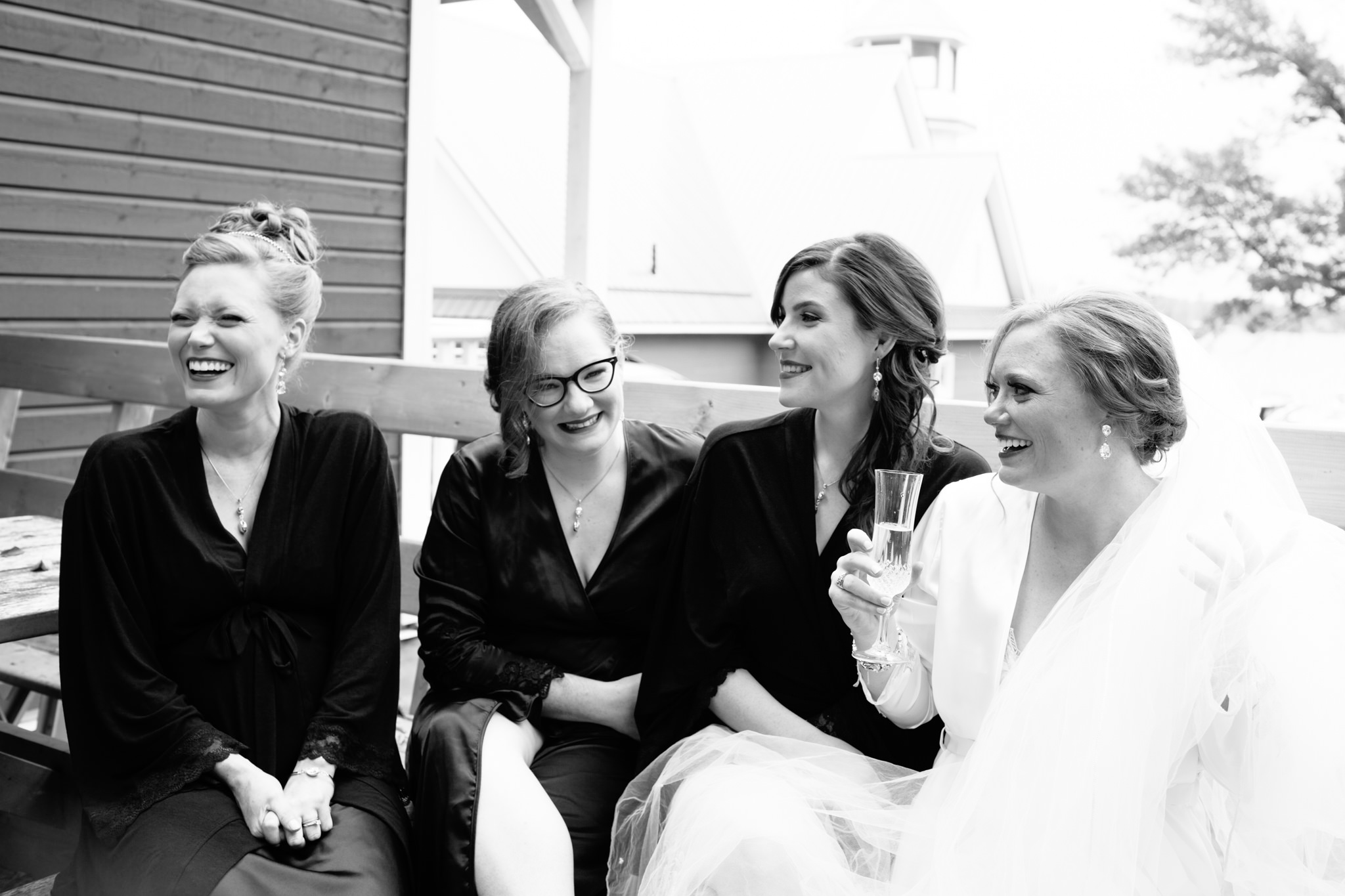 bride laughing with bridesmaids before ceremony