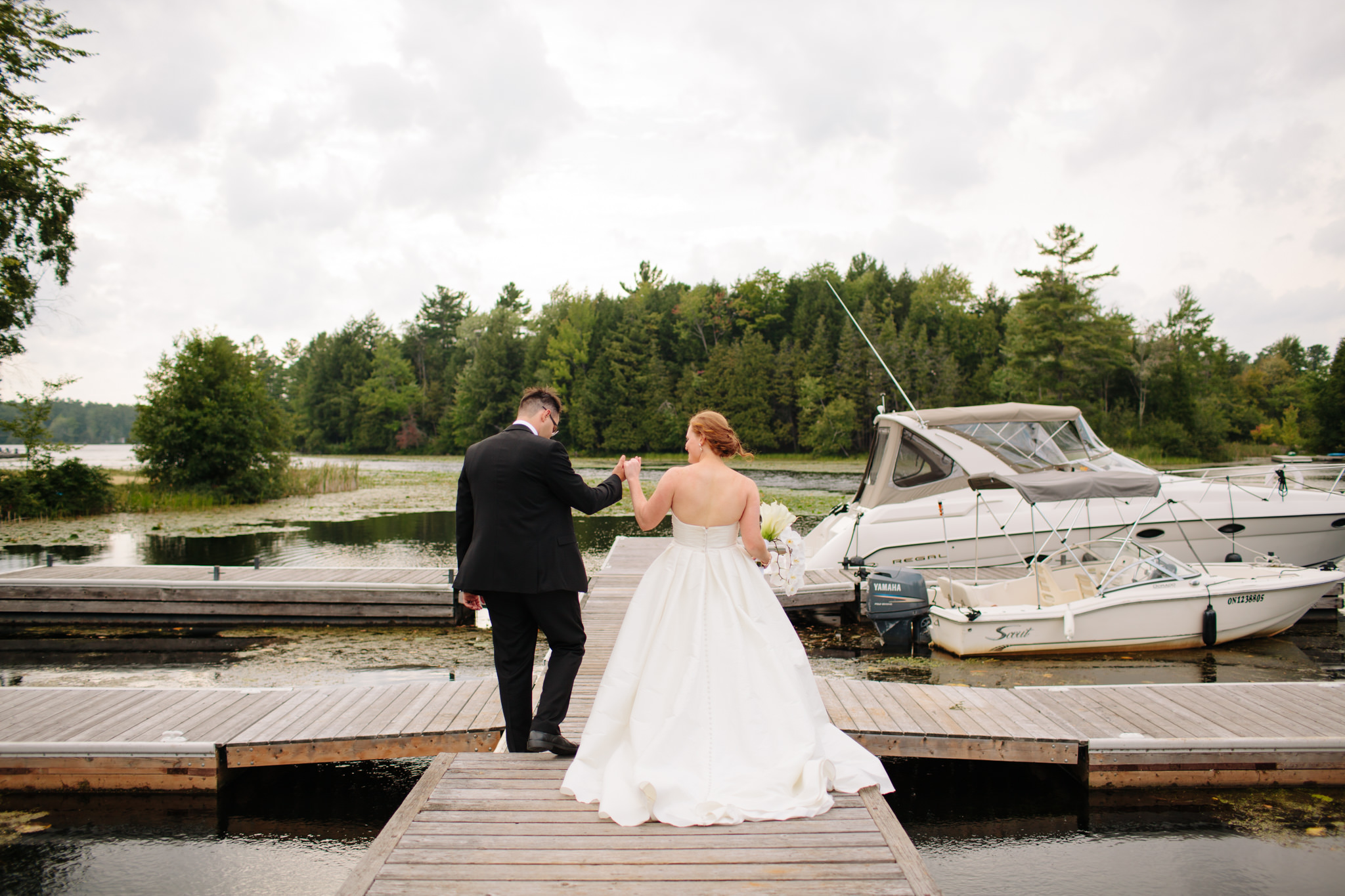 bride and groom walk down the dock after getting married