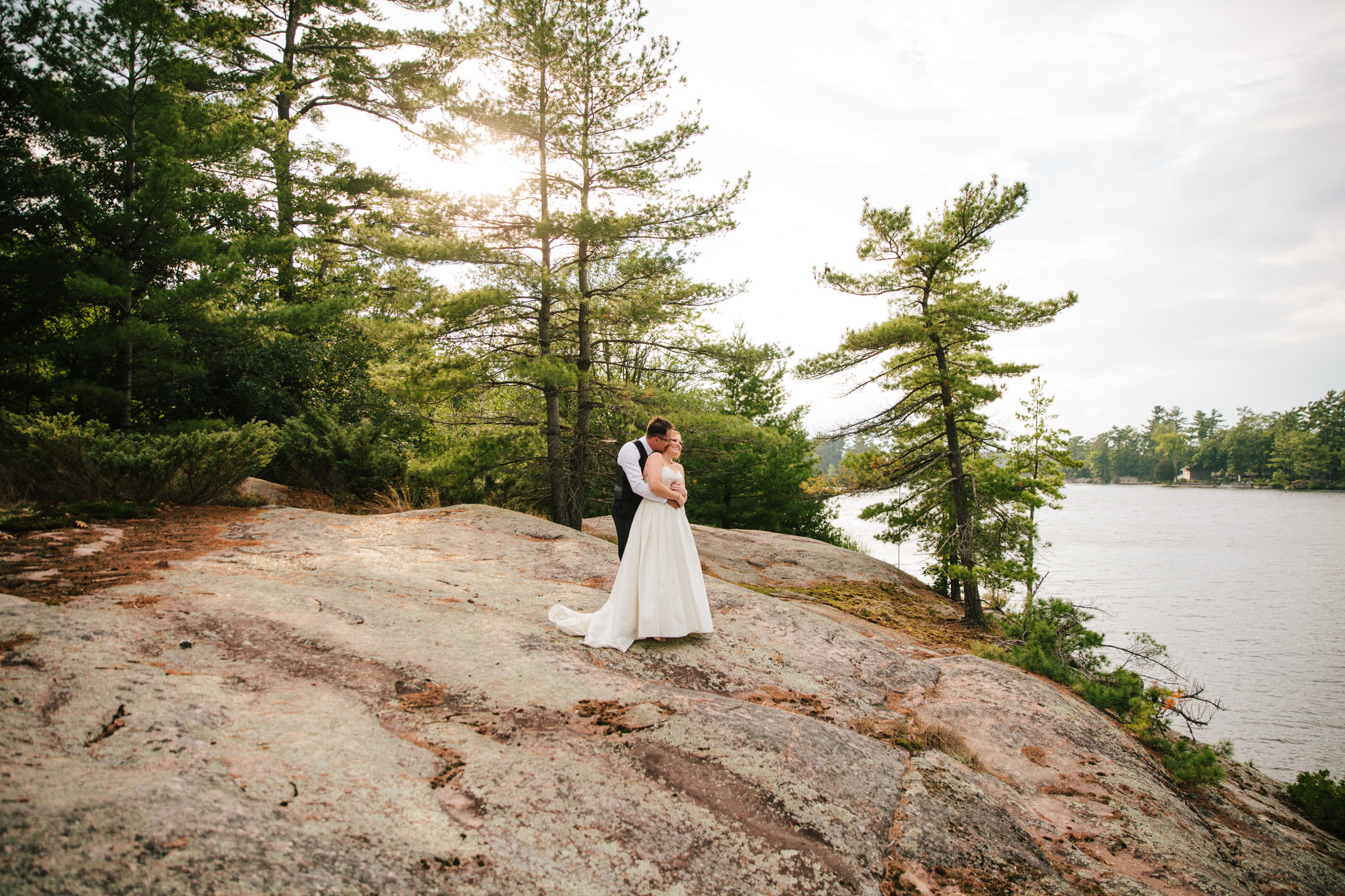 bride and groom hugging on island on Stony Lake