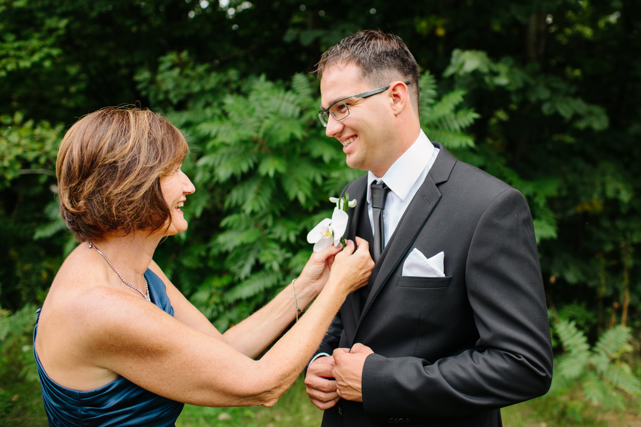 mother of groom putting on boutineer
