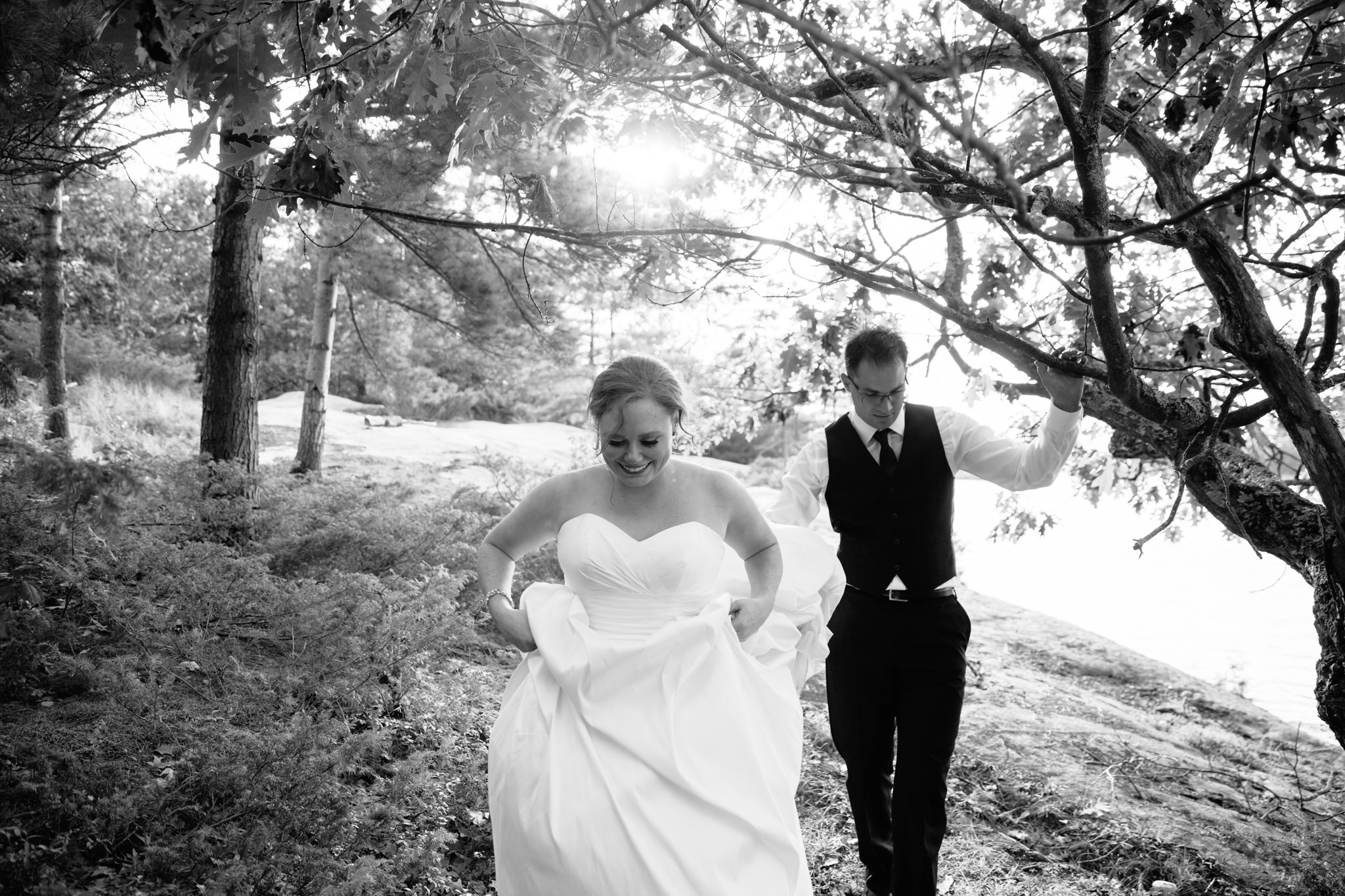 bride and groom walking on lakeside island wedding
