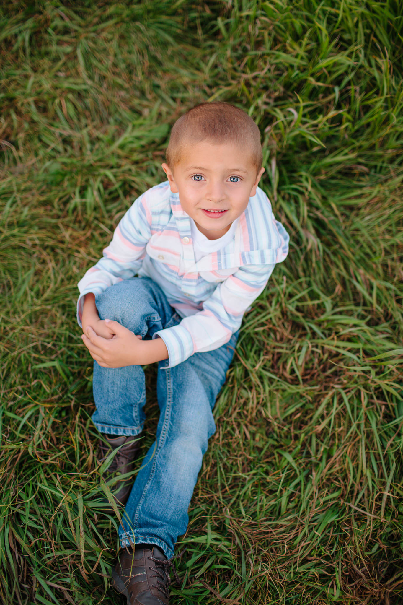 boy in grass smiling for portrait