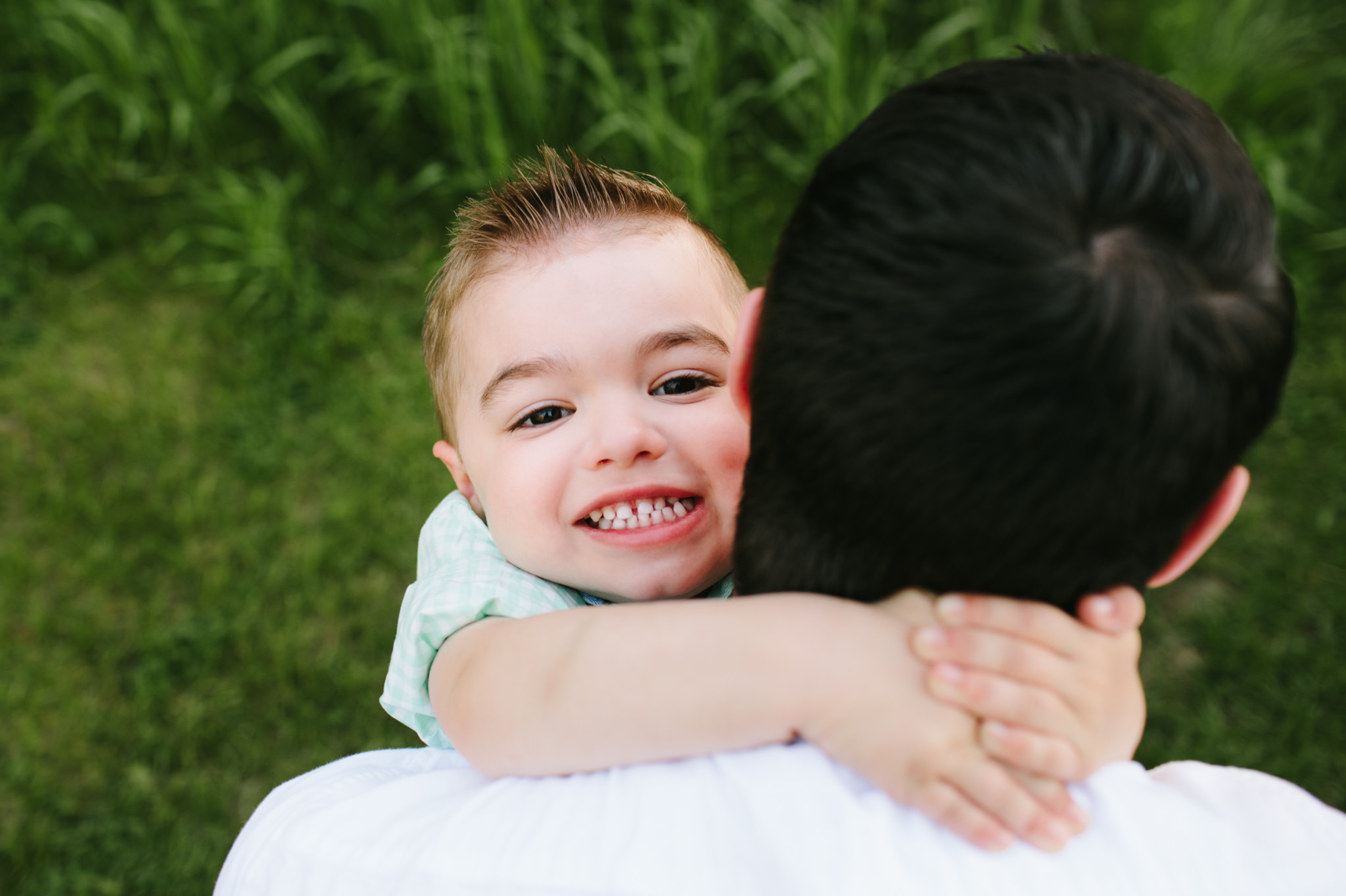 son hugging his father during family photo session