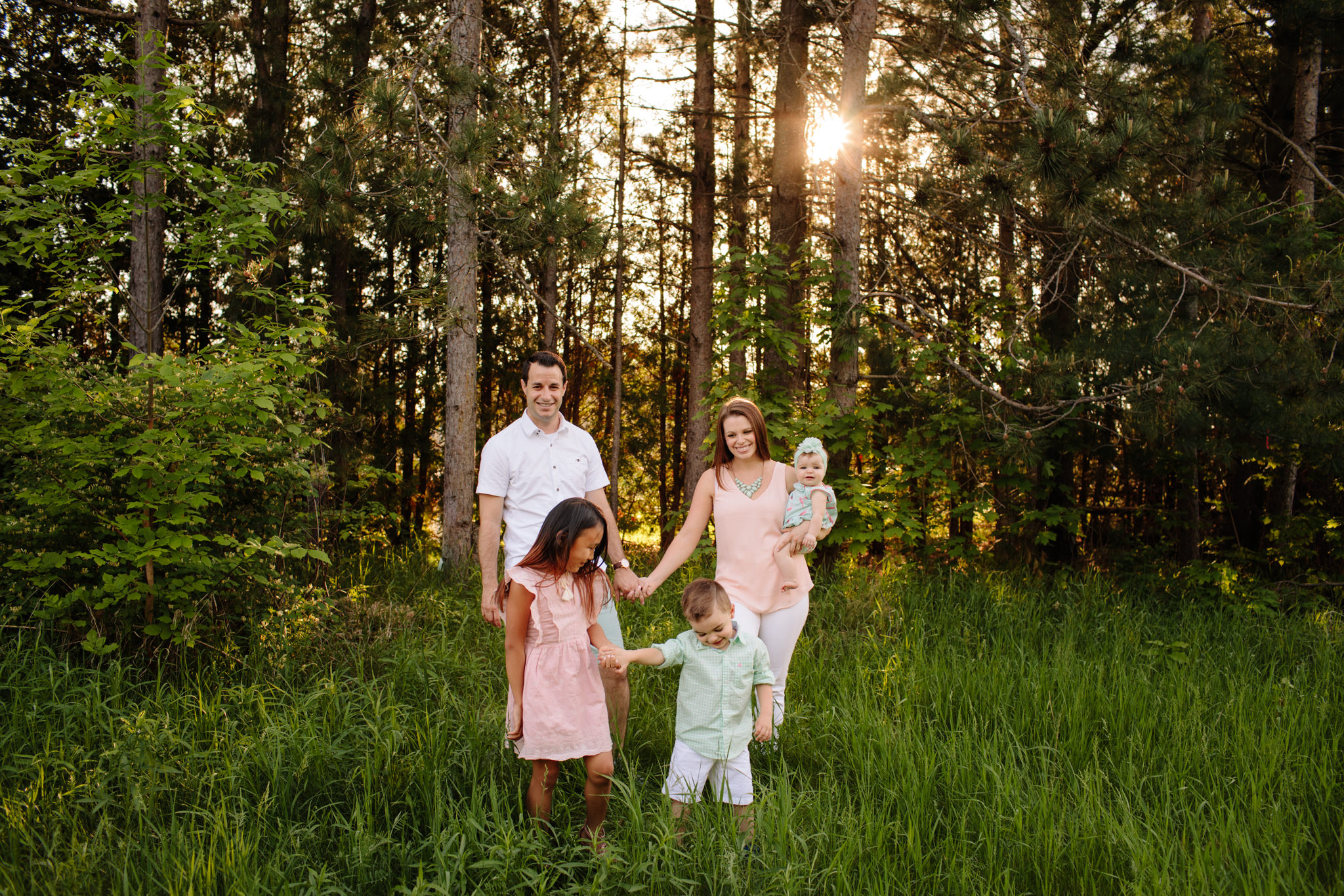 family walking through tall grass at sunset for photoshoot