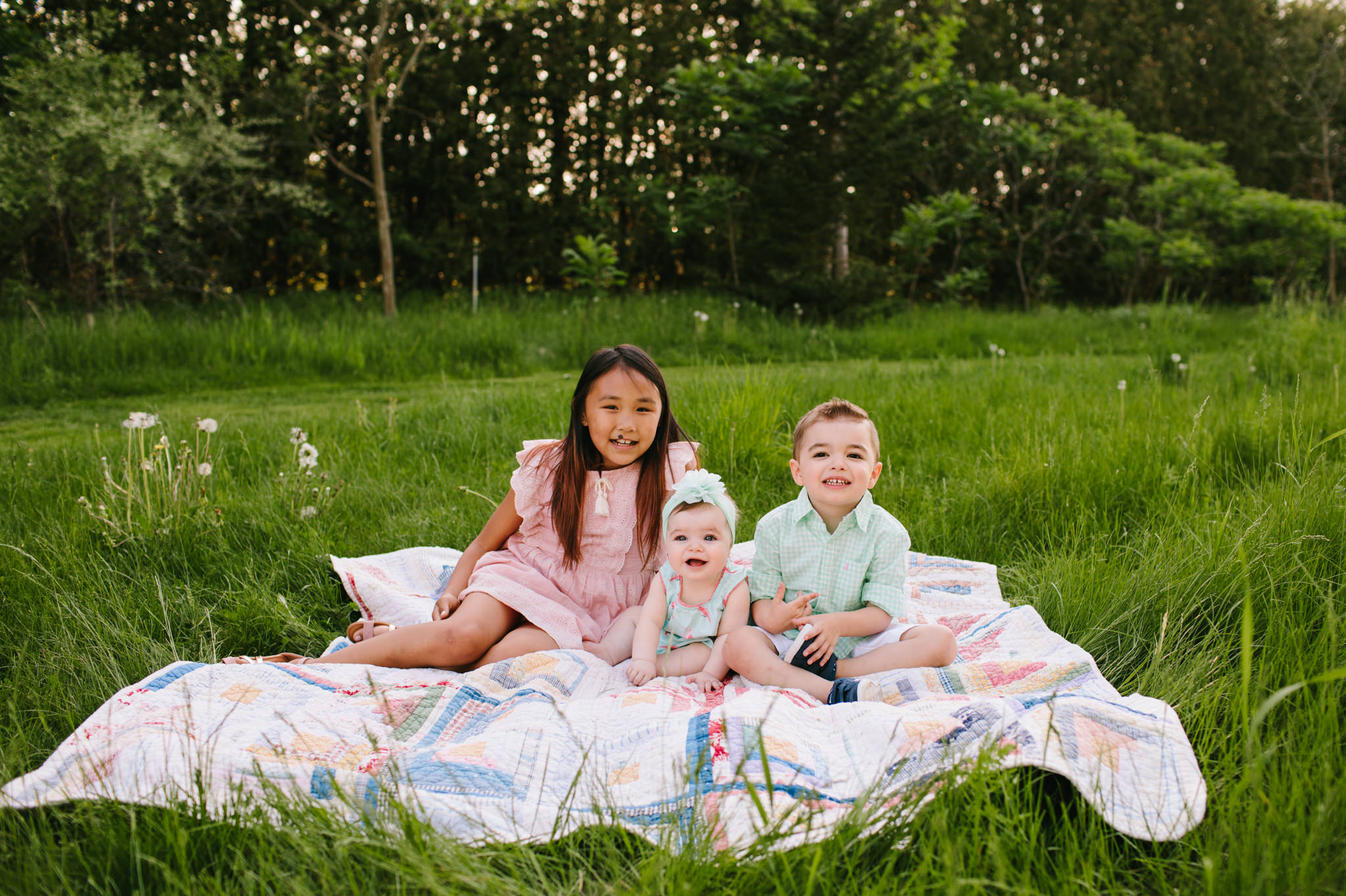siblings on an antique blanket for family photoshoot