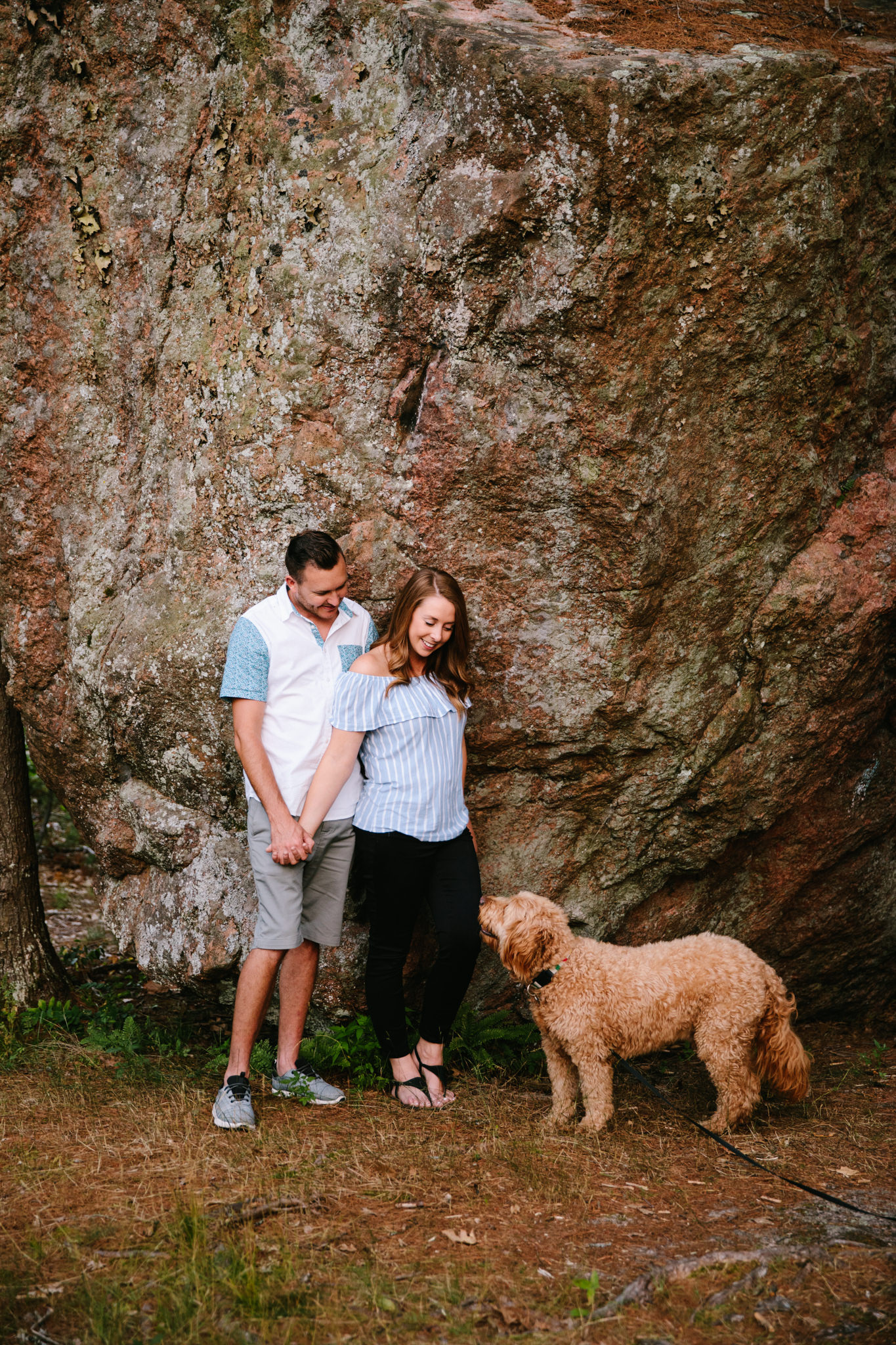 couple looking down at dog while standing infront of adam and eve rock