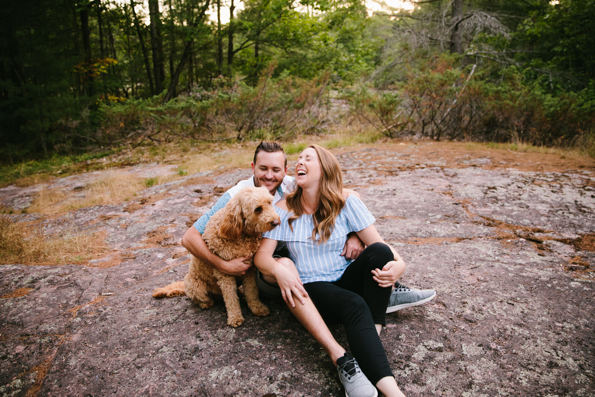 couple embracing each other and dog while sitting on a rock at sunset