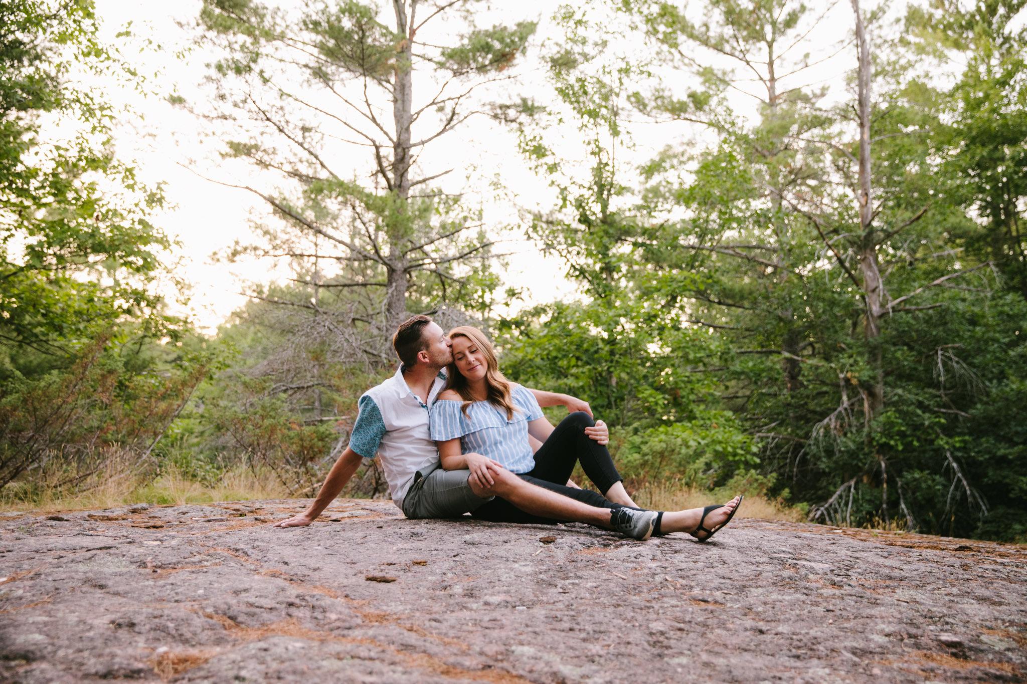 boy embracing girl while sitting on a rock called adam + eve buckhorn