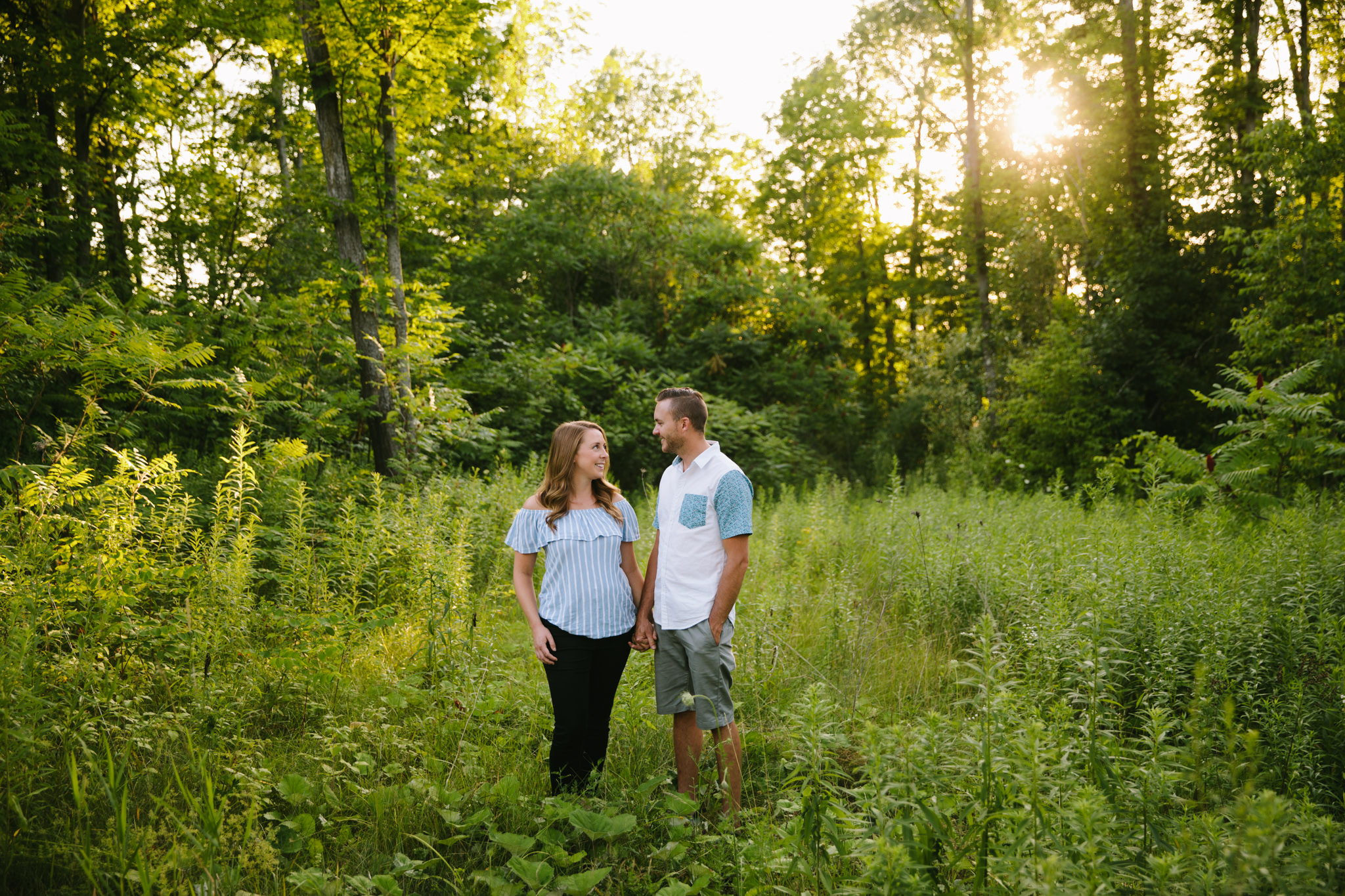couple photography session with a guy and girl holding hands in a green field at sunset