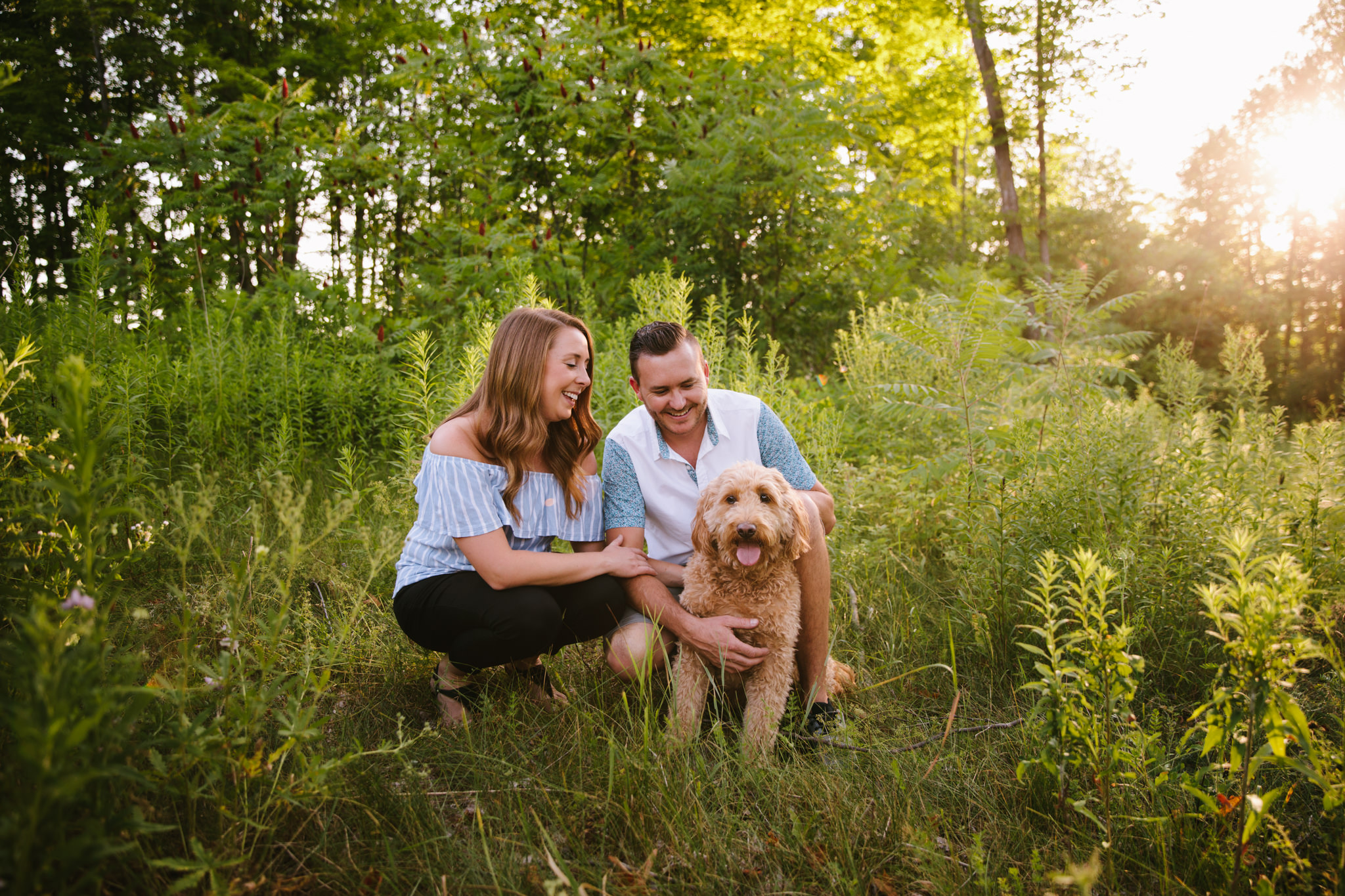 girl and guy cuddling while crouched around dog