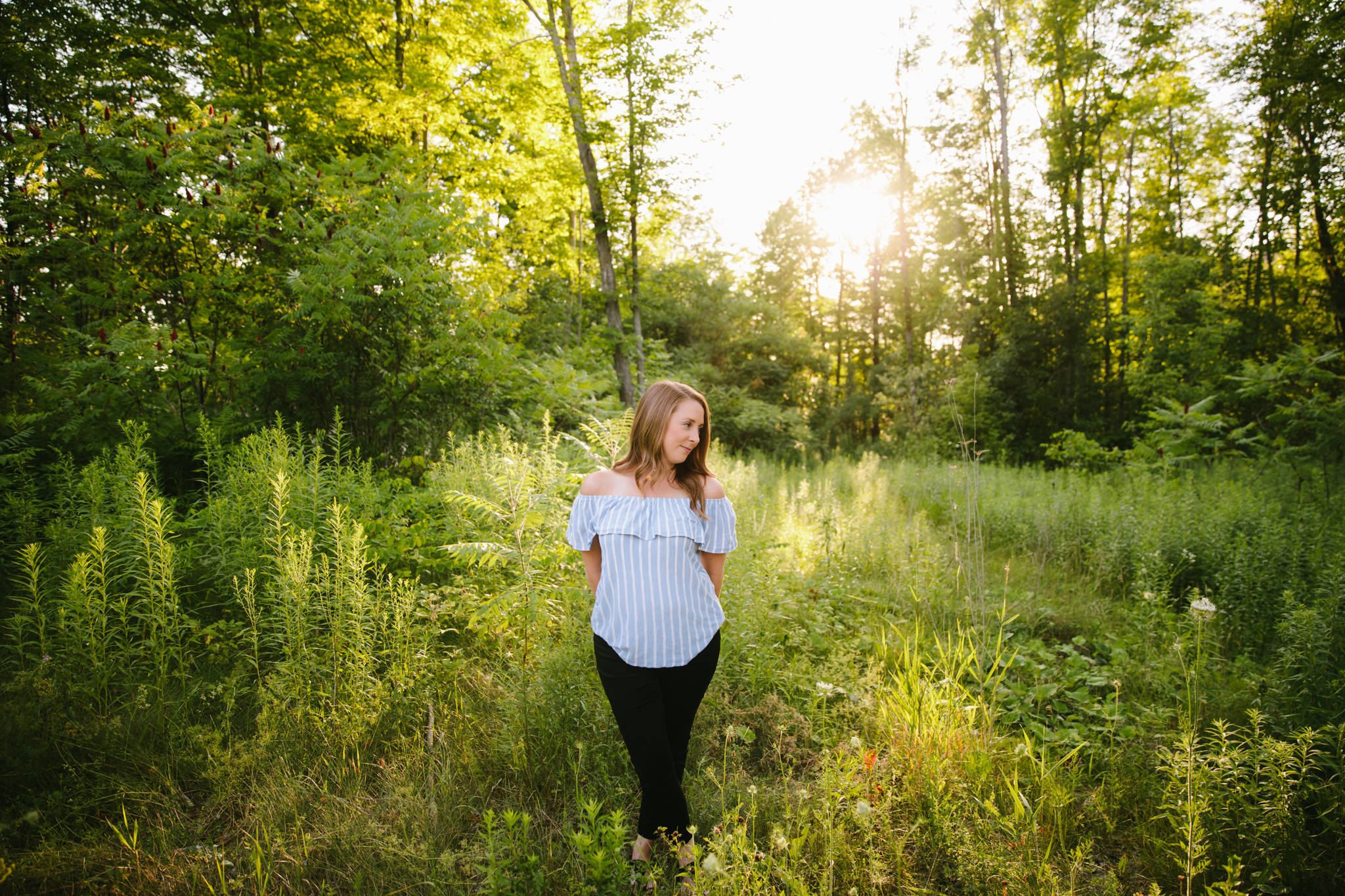girl looking to the side while standing in a field