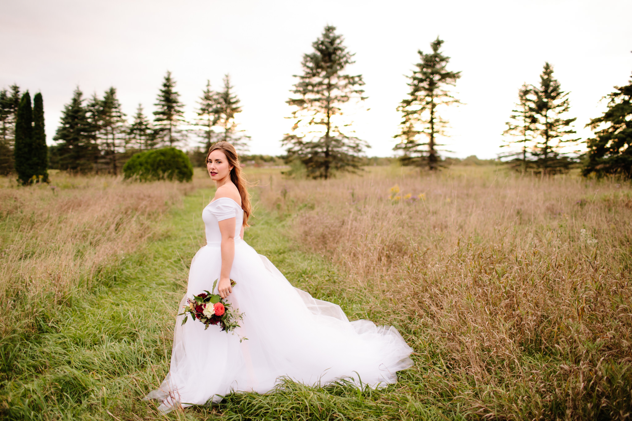 bride displaying large tulle white dress while standing in a field