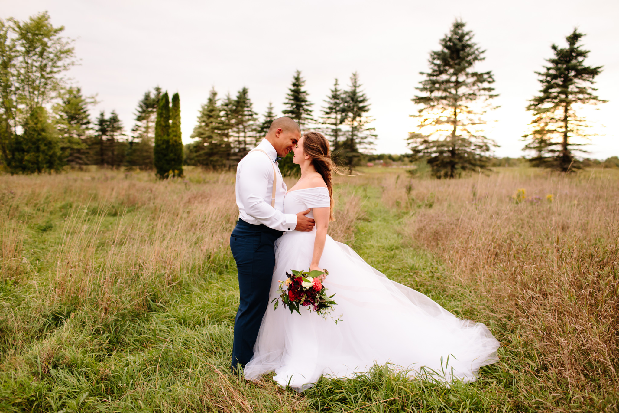 groom and bride kissing in kawartha lakes field during wedding session