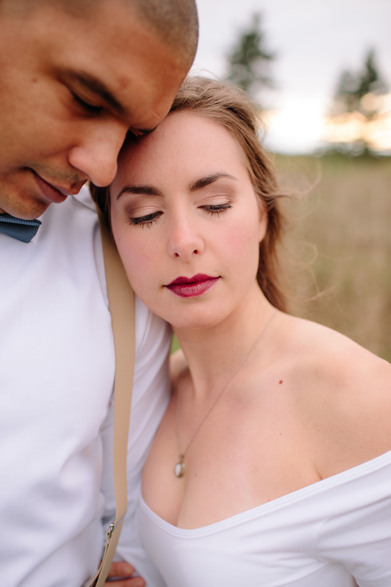 bride and groom cuddling displaying her makeup