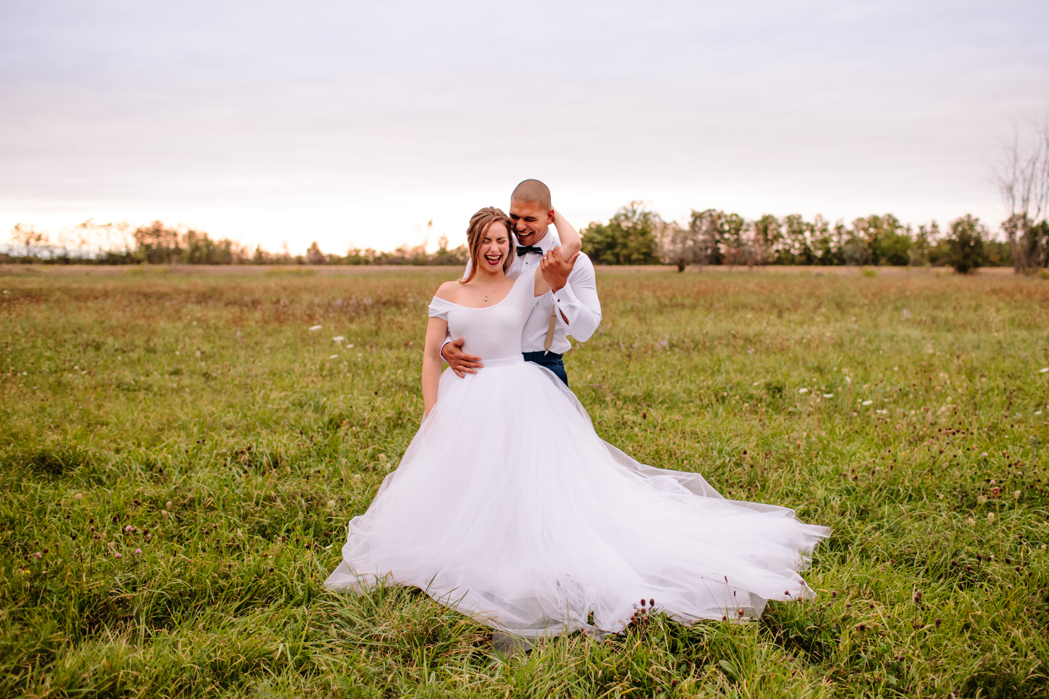 farm field with bride and groom standing and embracing