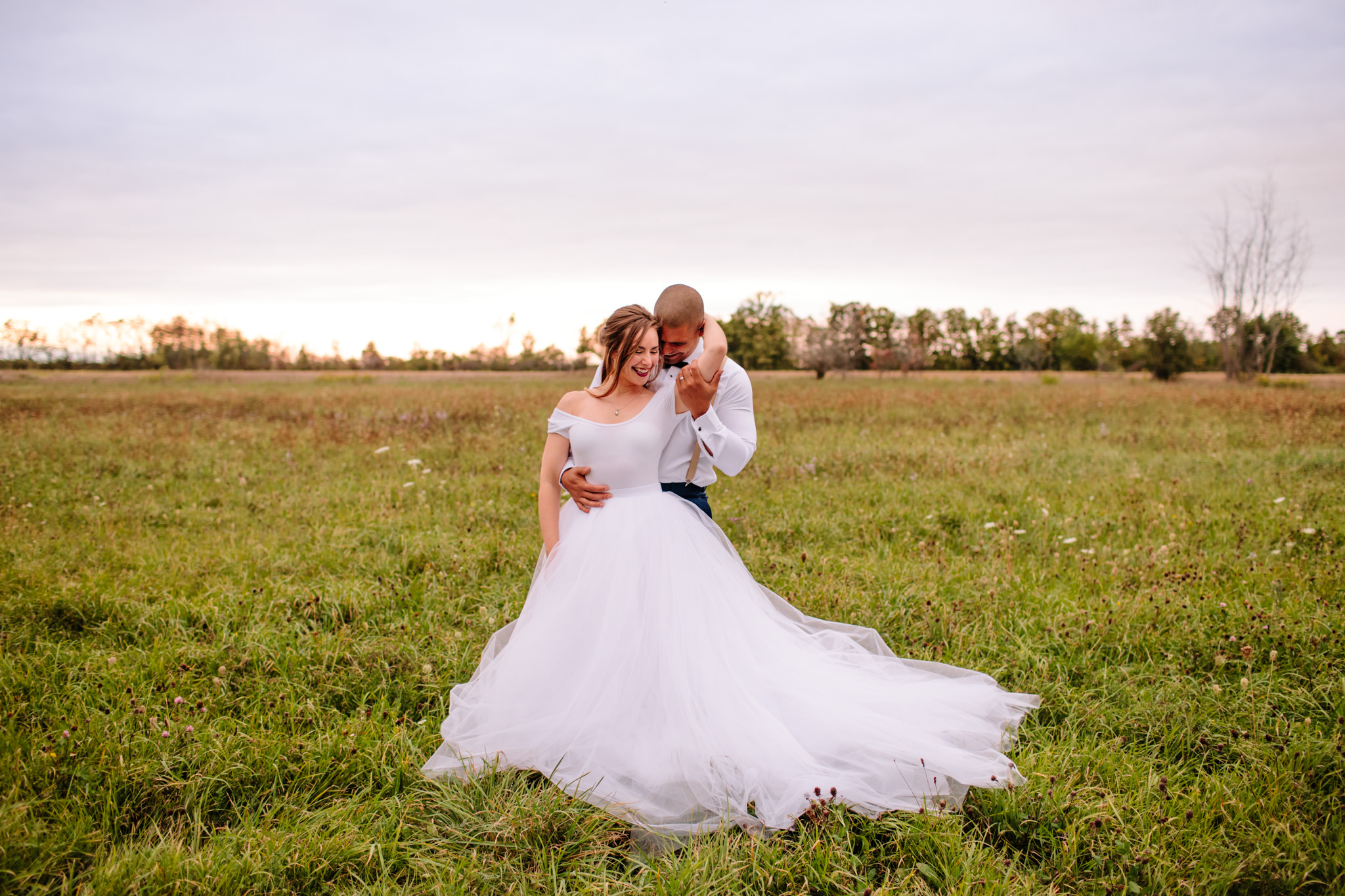 bride and groom in a embrace in a field