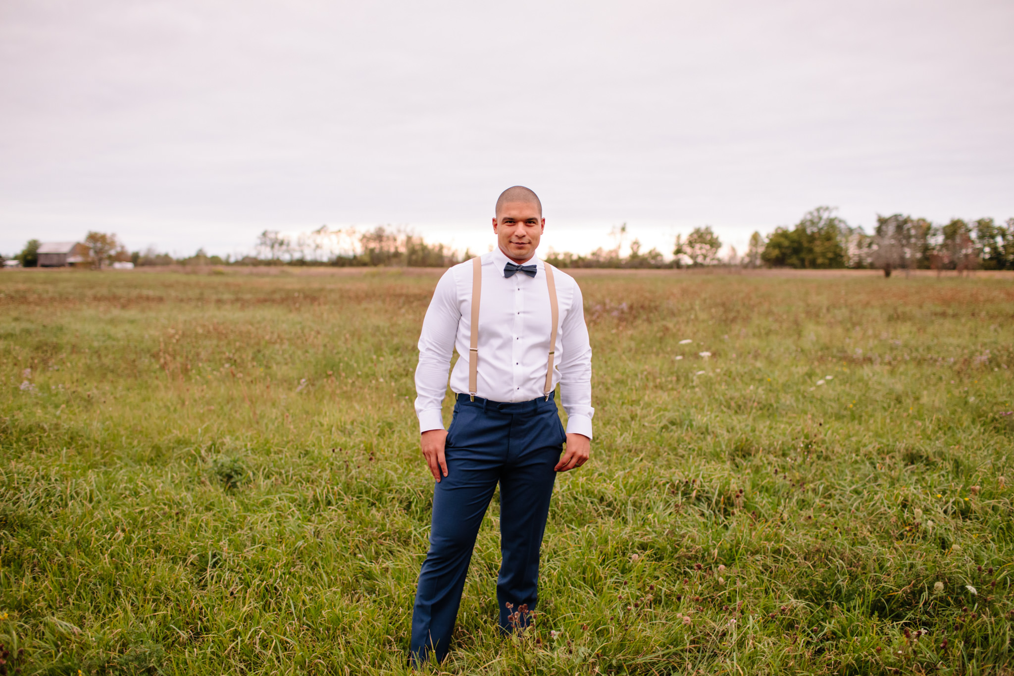 groom in navy pants and suspenders standing in a field for wedding portrait