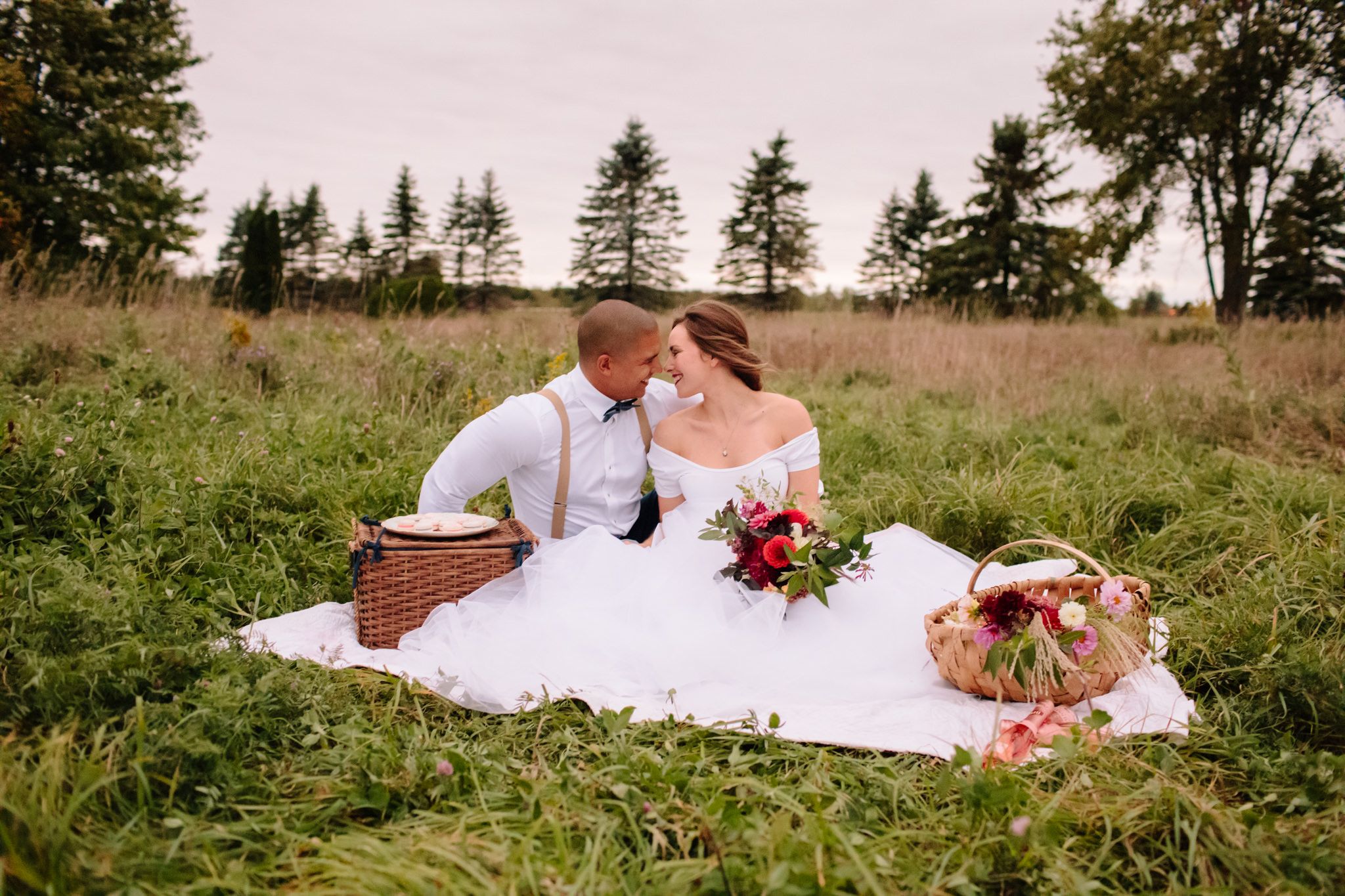 bride and groom having a wedding picnic in a field