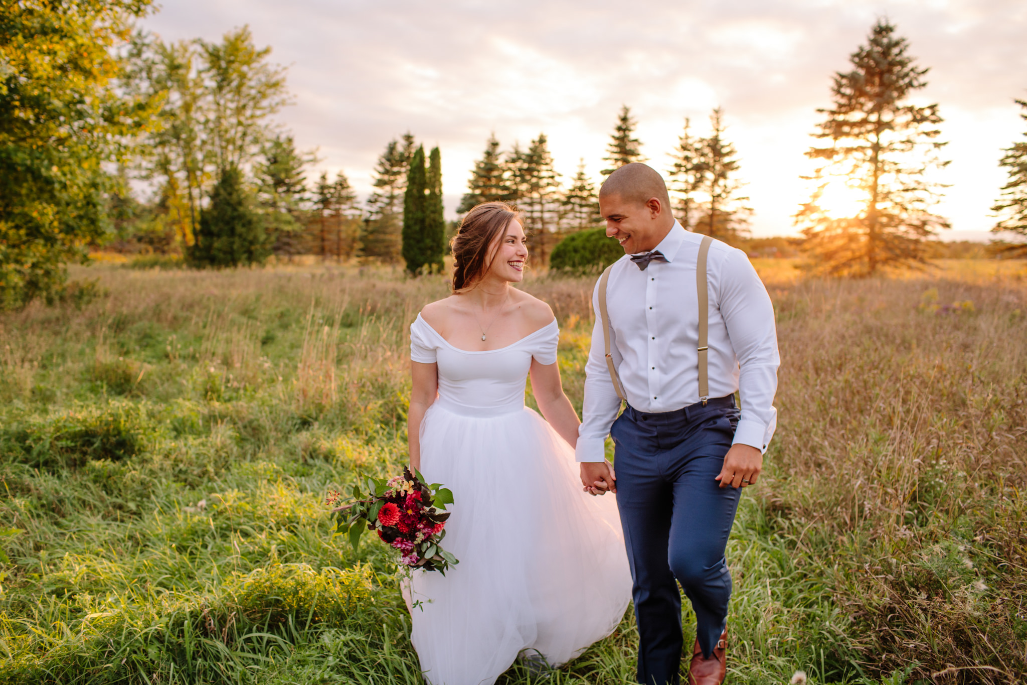 bride and groom holding hands walking through a field